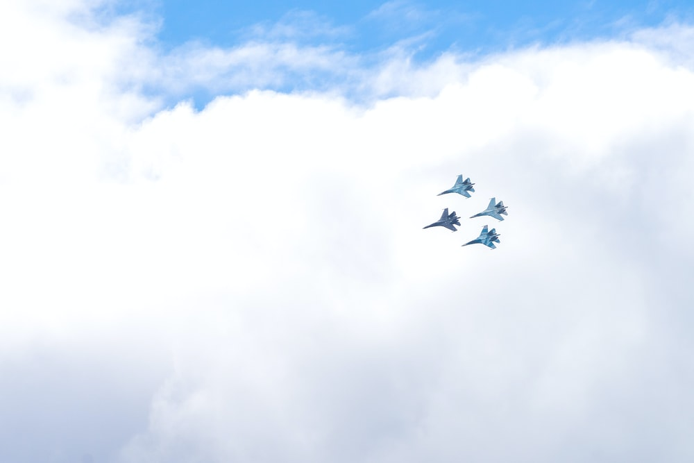 four blue fighting planes surrounded white clouds