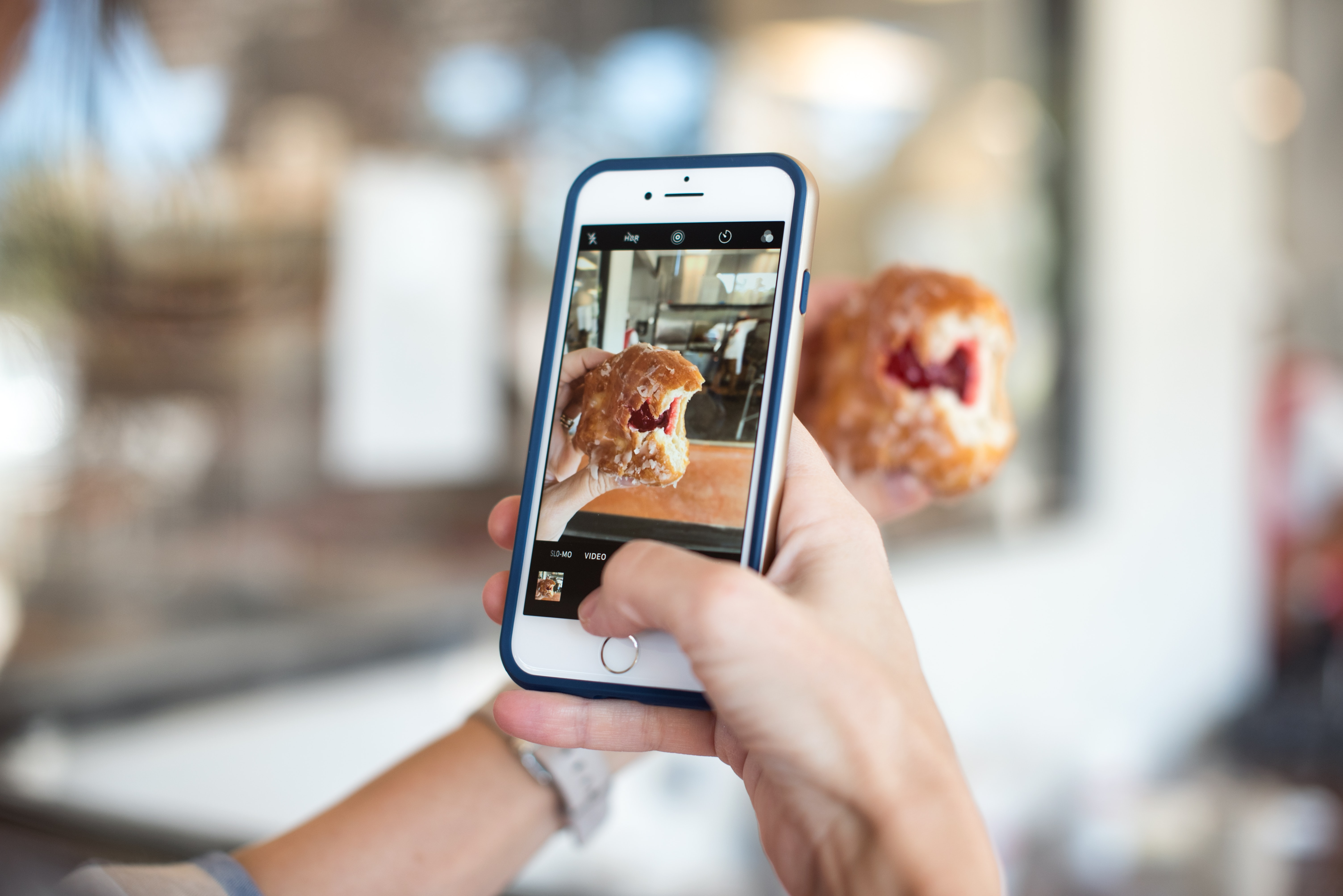 selective focus photography of person taking picture of brown food