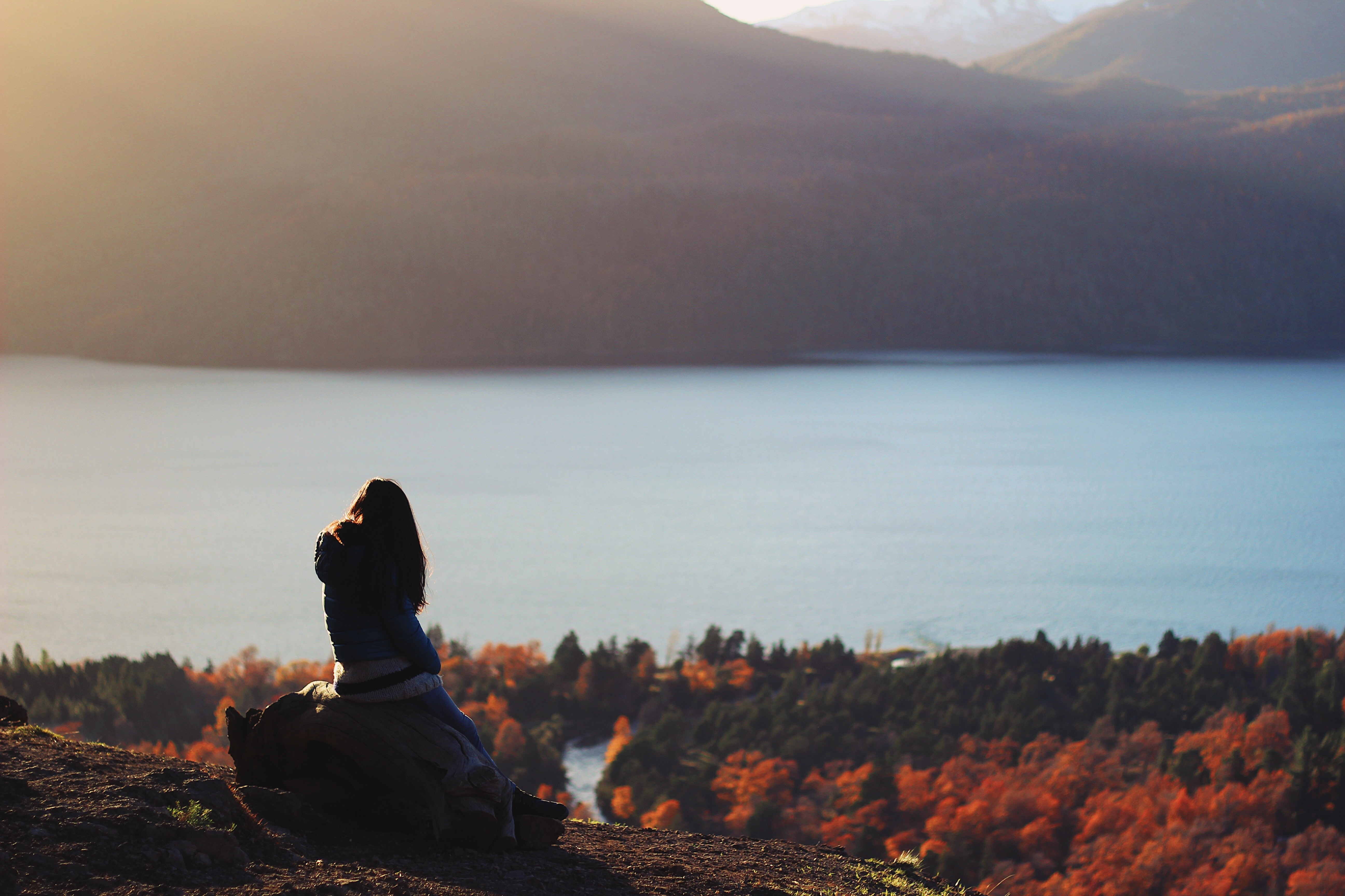 A woman wearing a winter coat sitting on a rock looking at the mountains, lake, and forest in Quilaquina