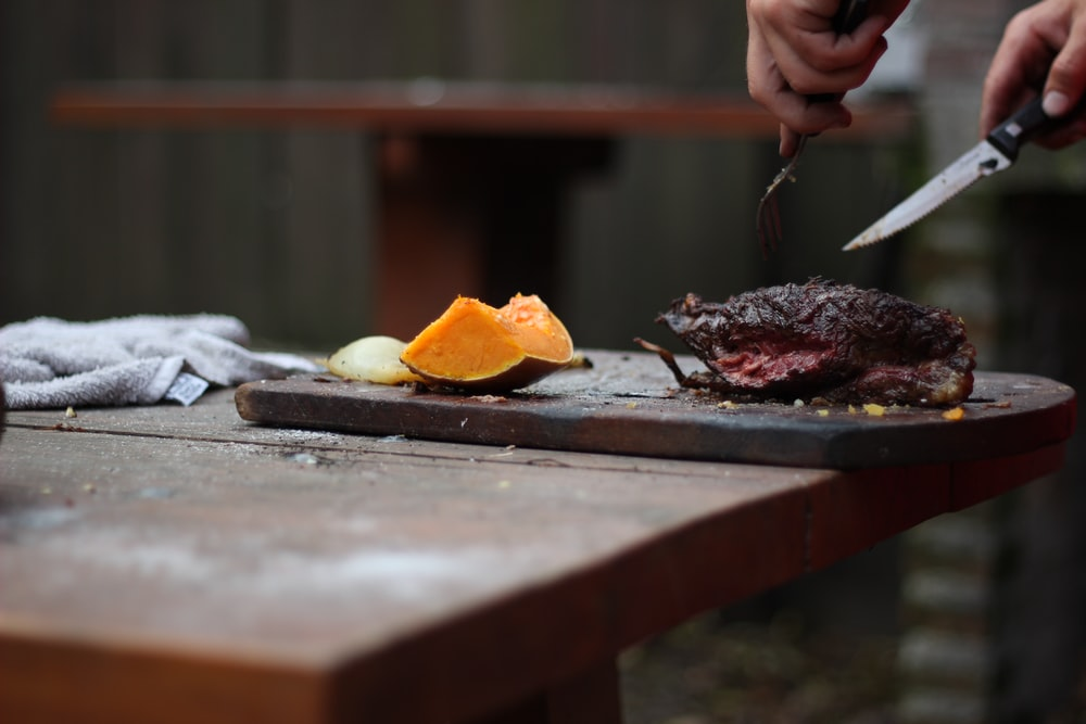 person slicing a meat using knife and fork