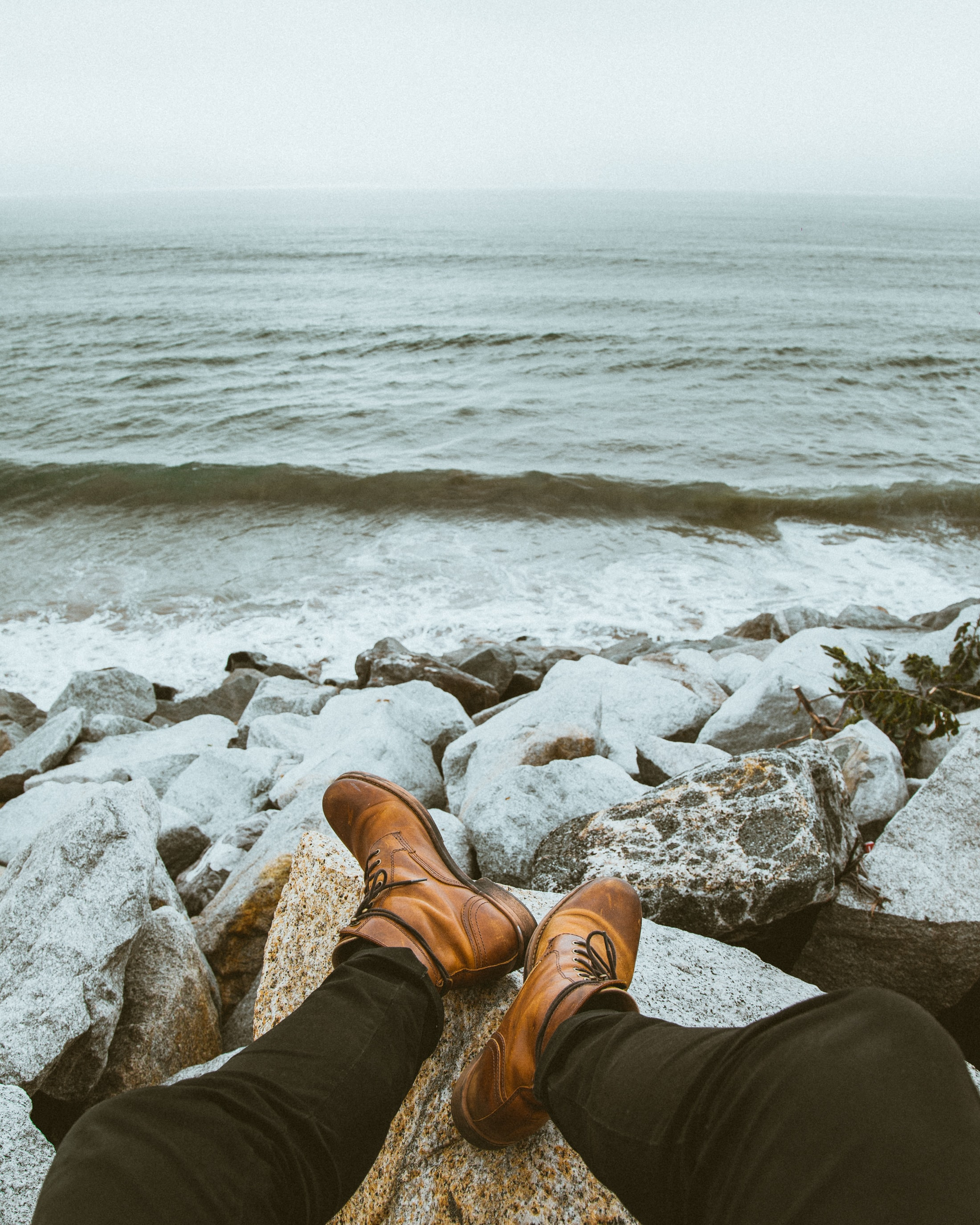 A person wearing black jeans and boots sitting on rocks near the water