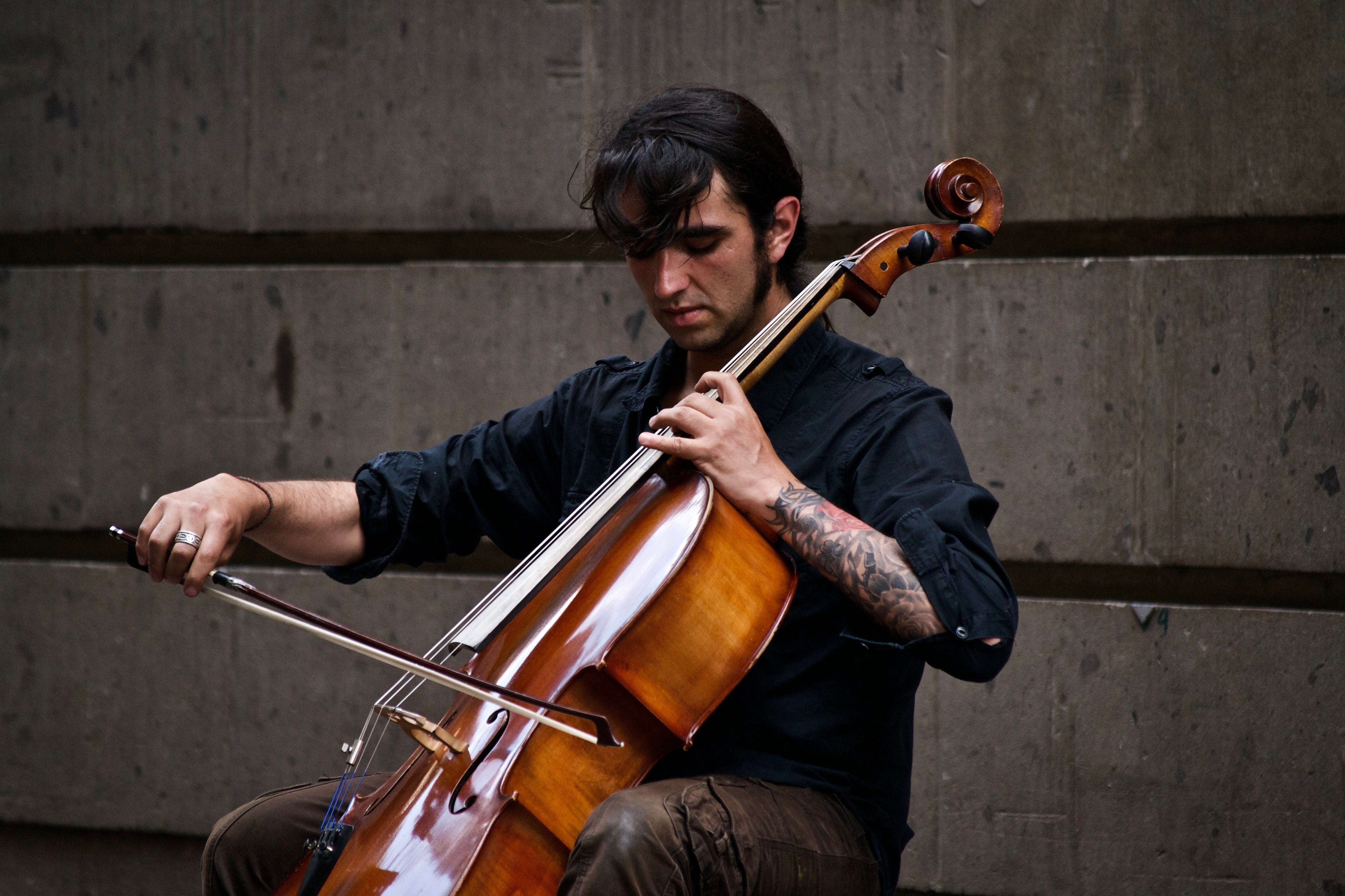 A man with a tattoo playing a cello in front of a wall
