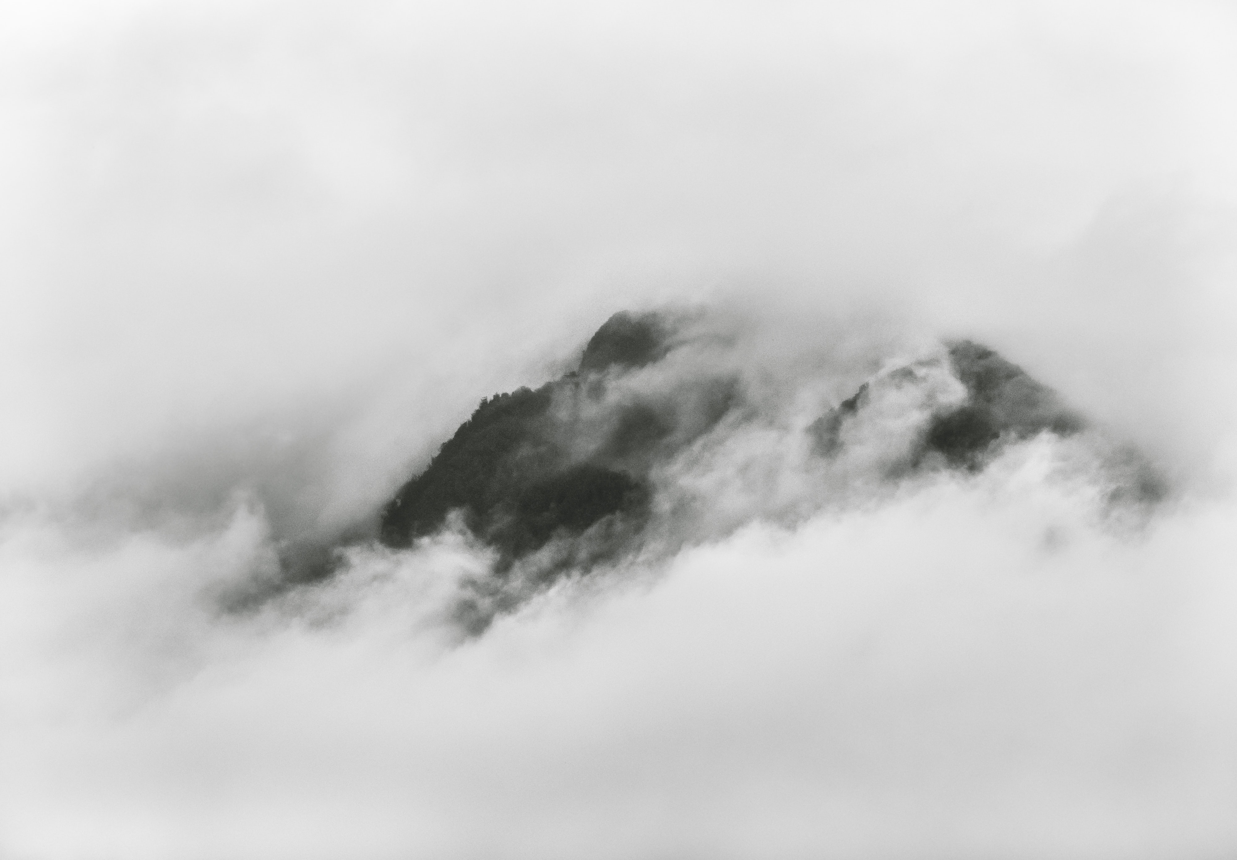 Misty mountains peek through clouds on an overcast day on the west coast