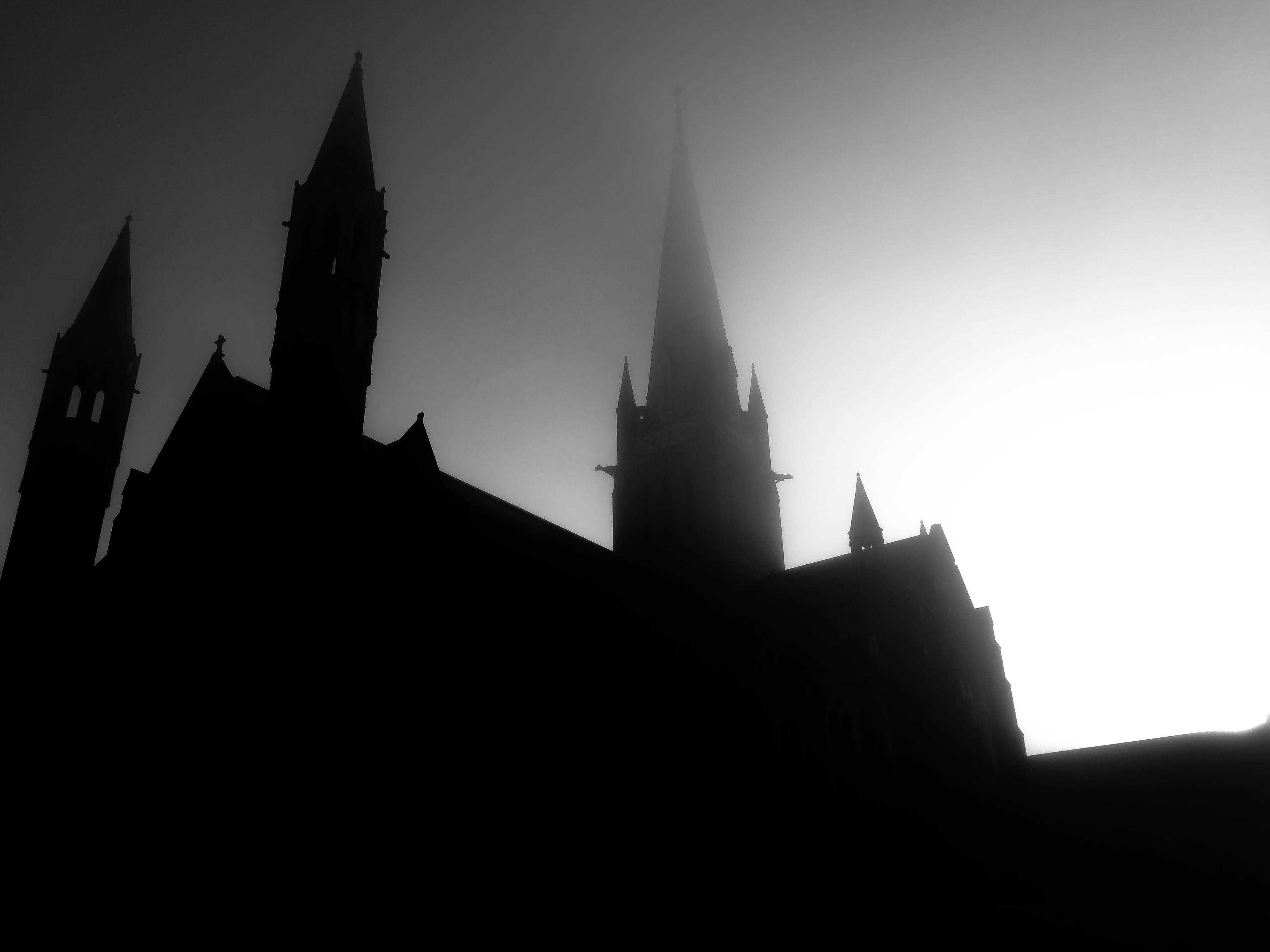 A silhouette of a castle like building with a gray and white sky.