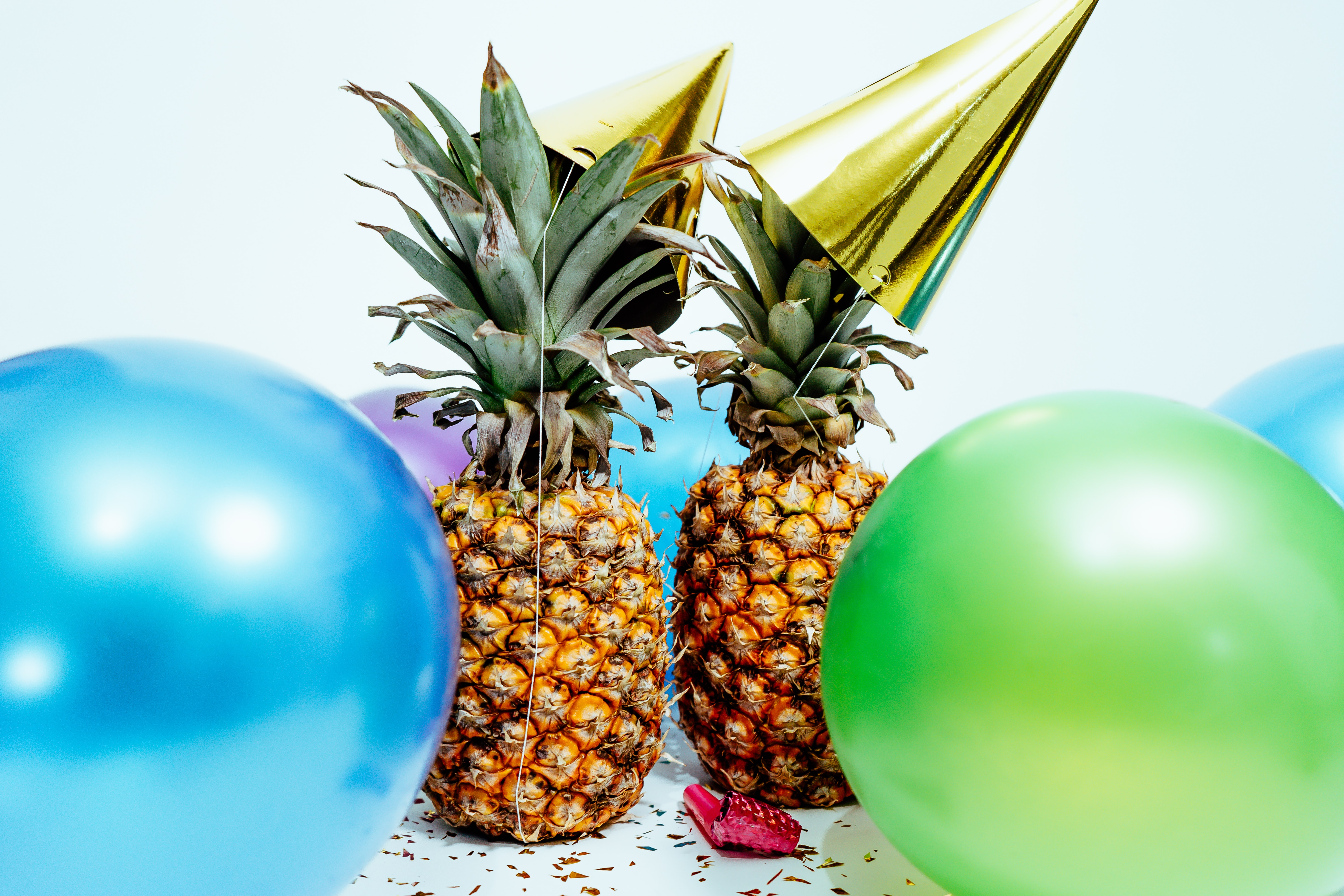 Two pineapples wearing party hats, surrounded by balloons, by Scott Webb Photography