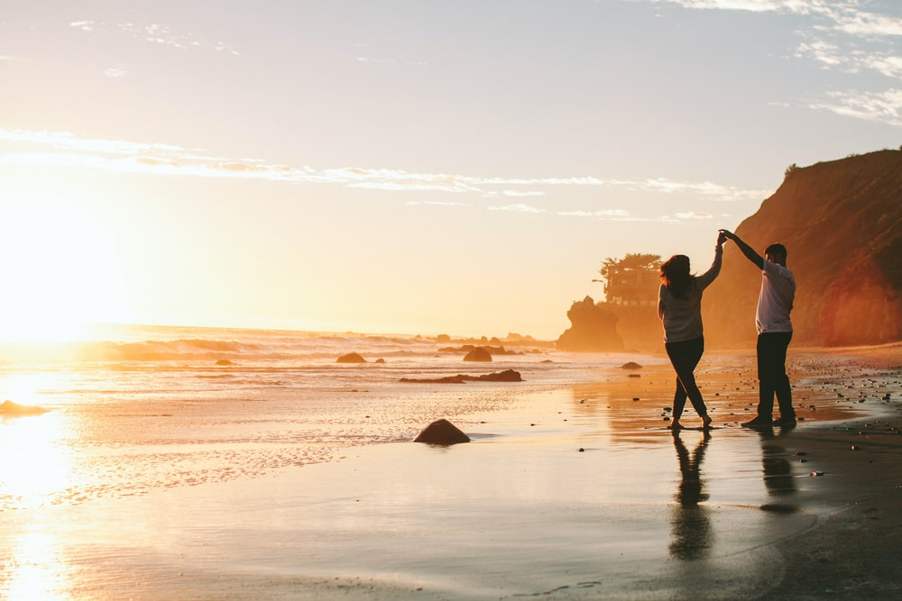 woman and man holding hands while standing on shore during golden hour