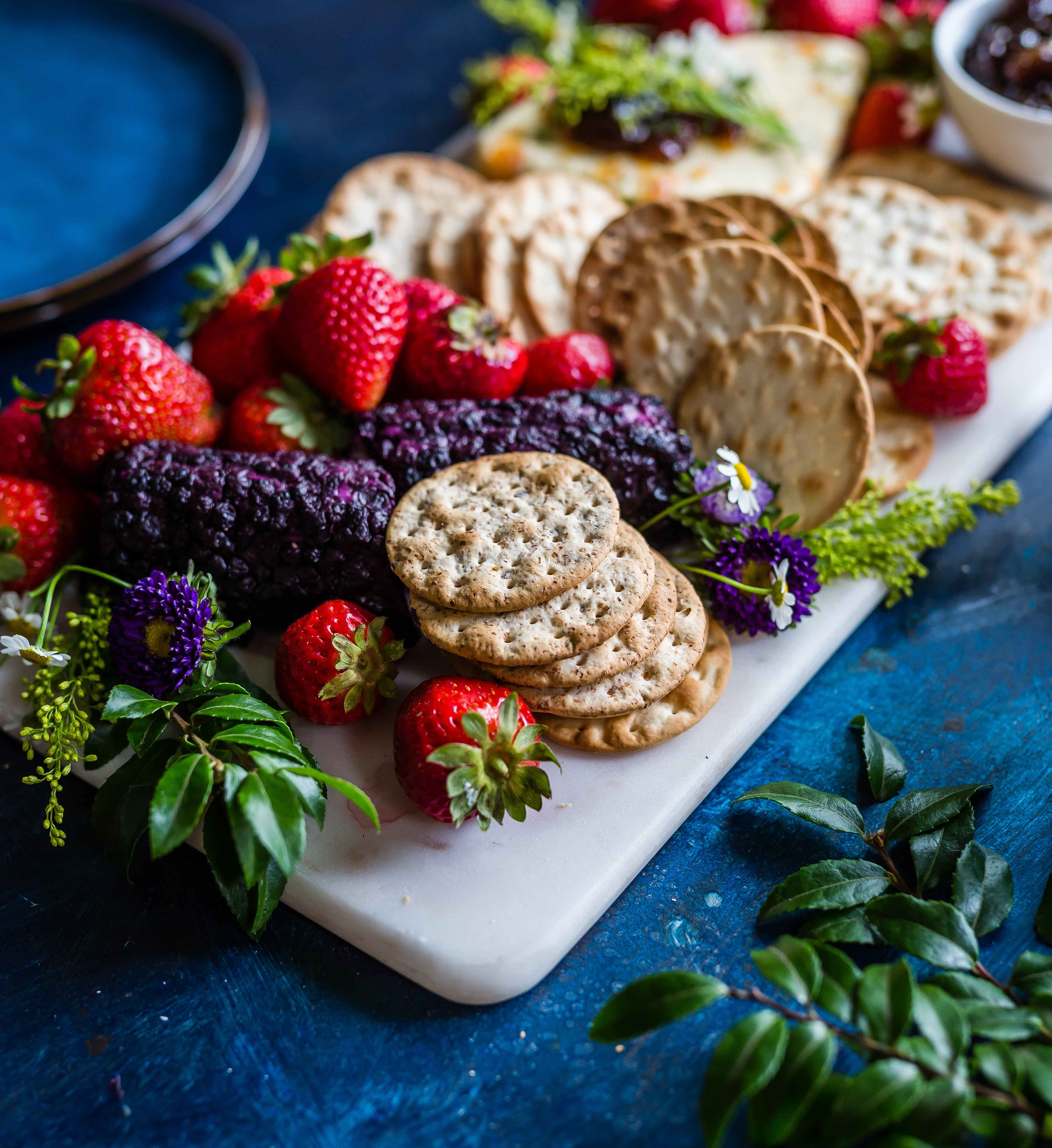 Cheeseboard with fruit, herbs, and crackers