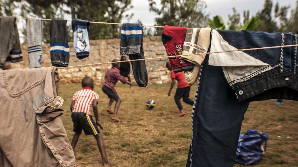 two boys playing under clothesline