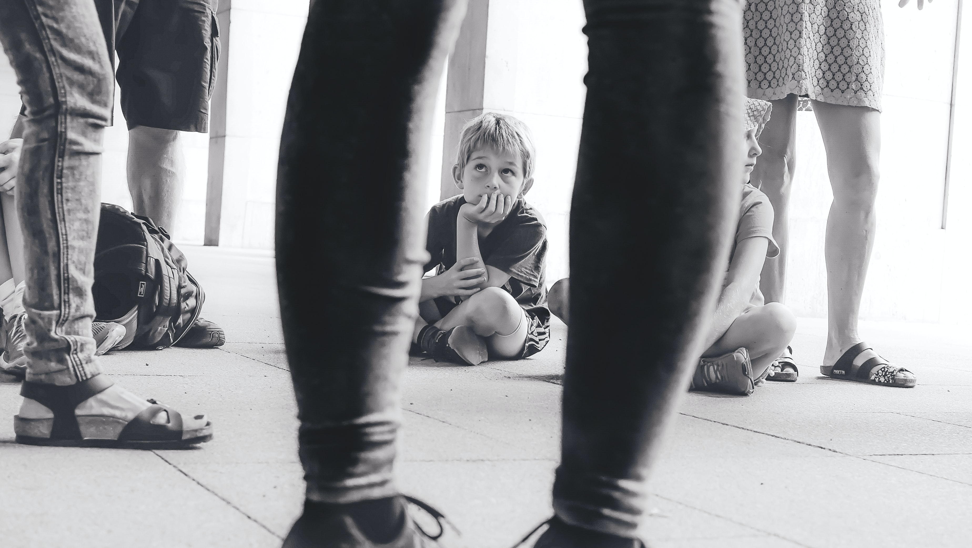grayscale photography of boy sitting on the floor watching the person in front of him