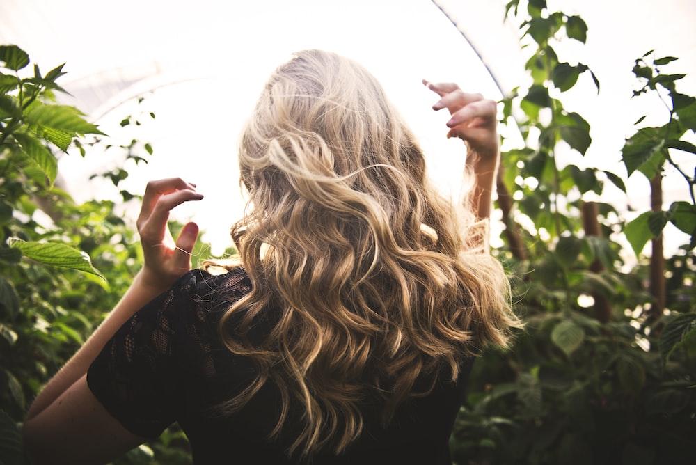 Mujer de pelo rubio en top negro rodeado de plantas altas