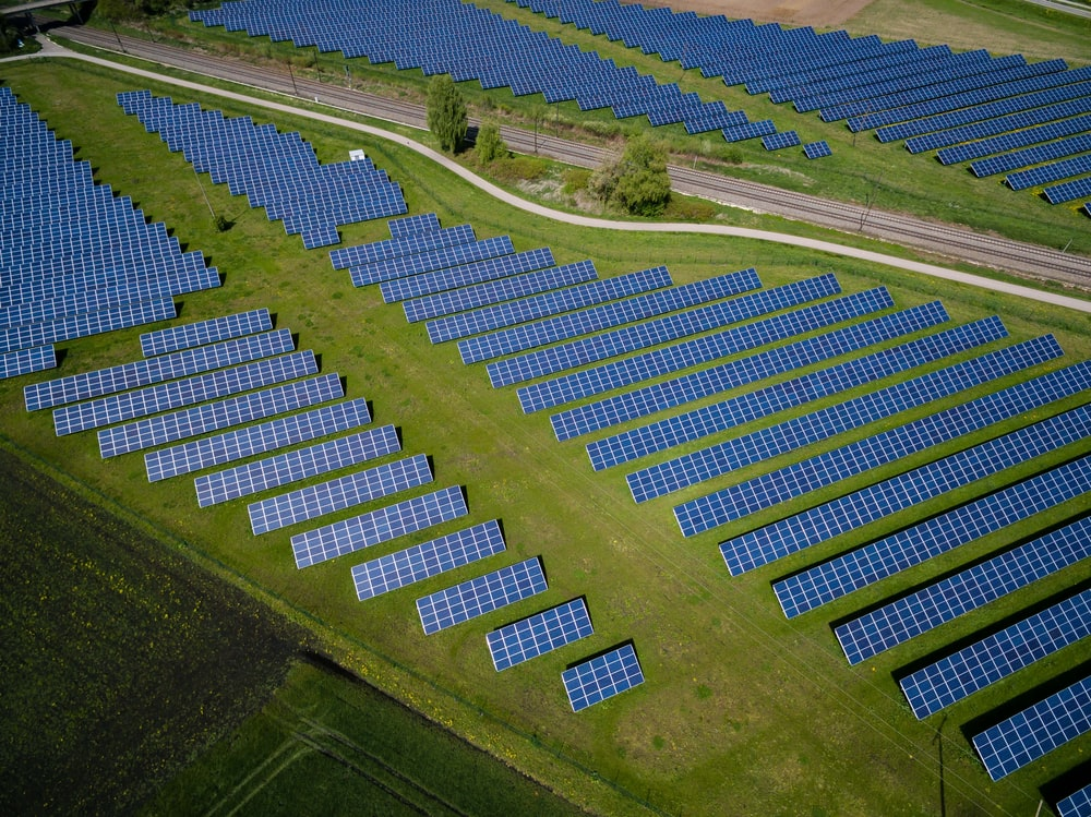 aerial photography of grass field with blue solar panels