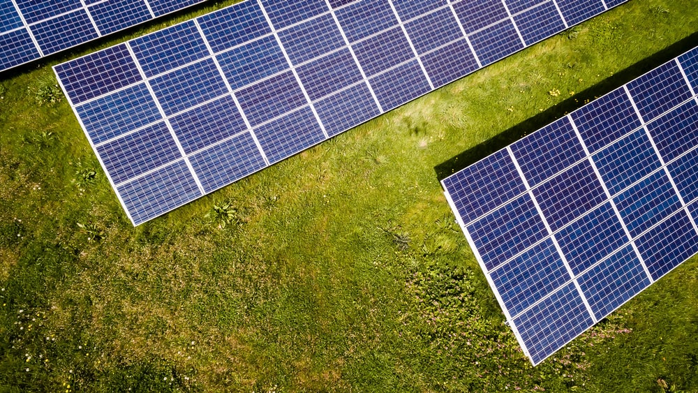A drone shot of solar panels on a green lawn