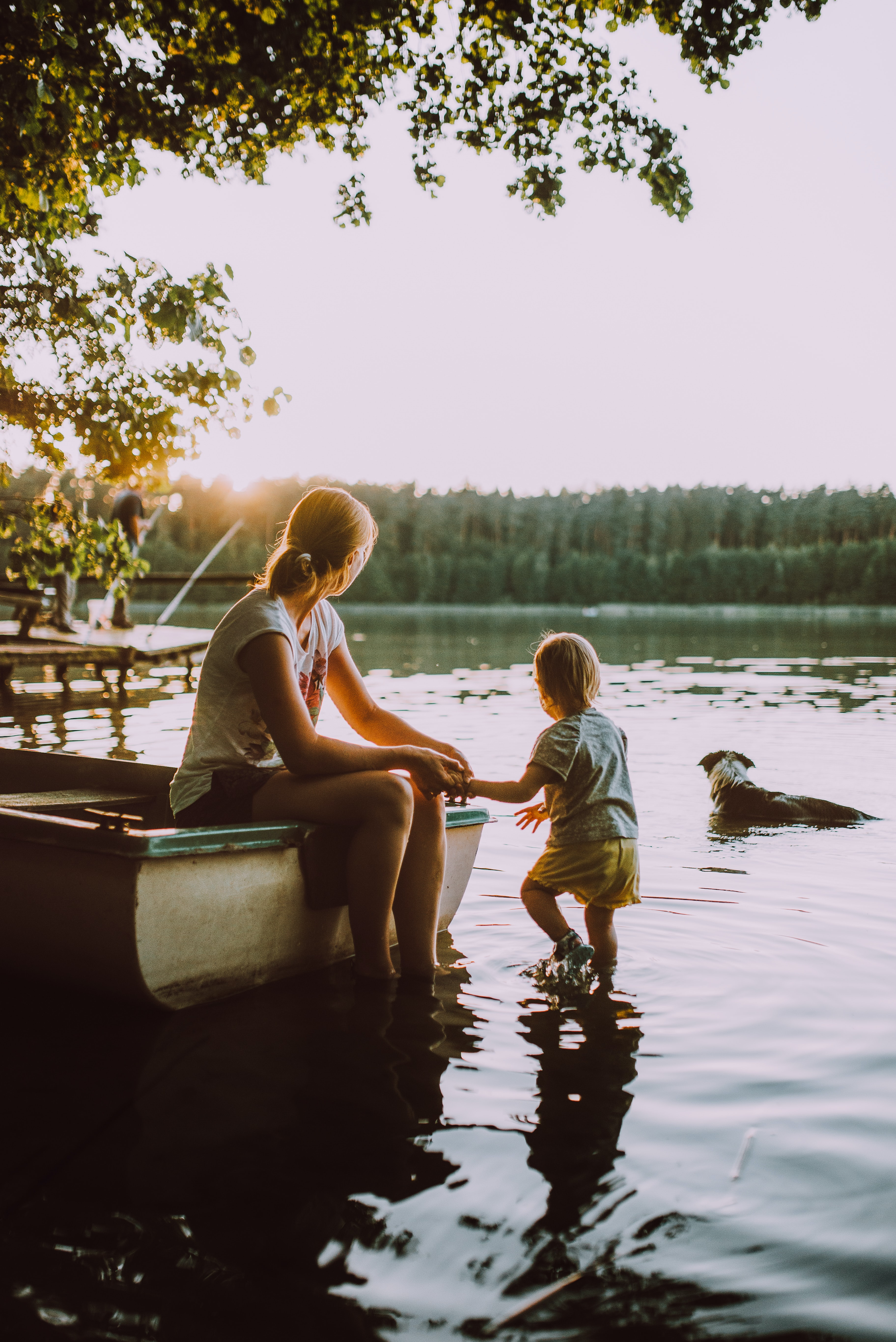 Young mother dangles feet into water's edge while child and dog look off into a lake.