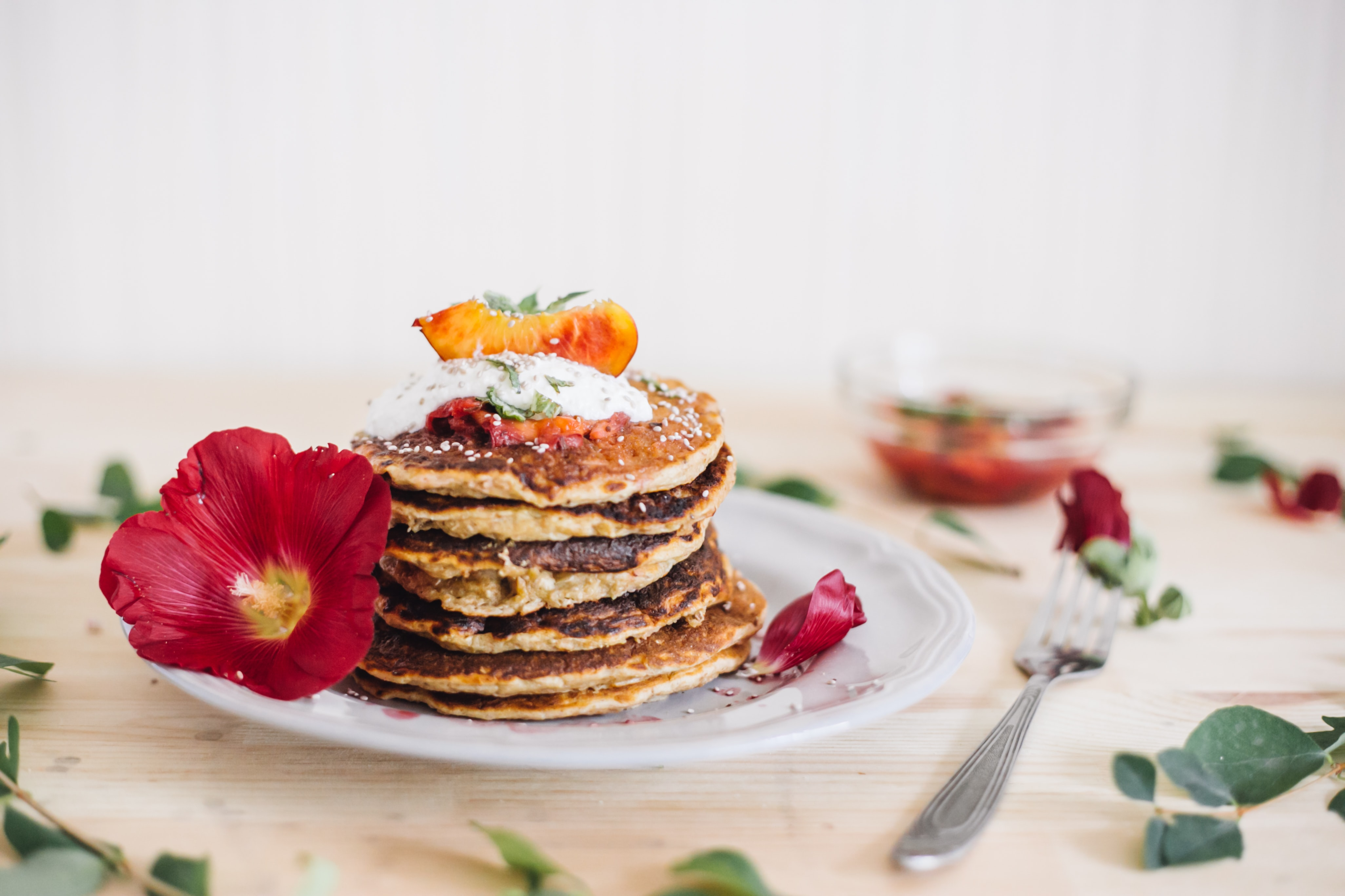 A stack of breakfast pancakes on a plate with red flowers and petals as a decoration