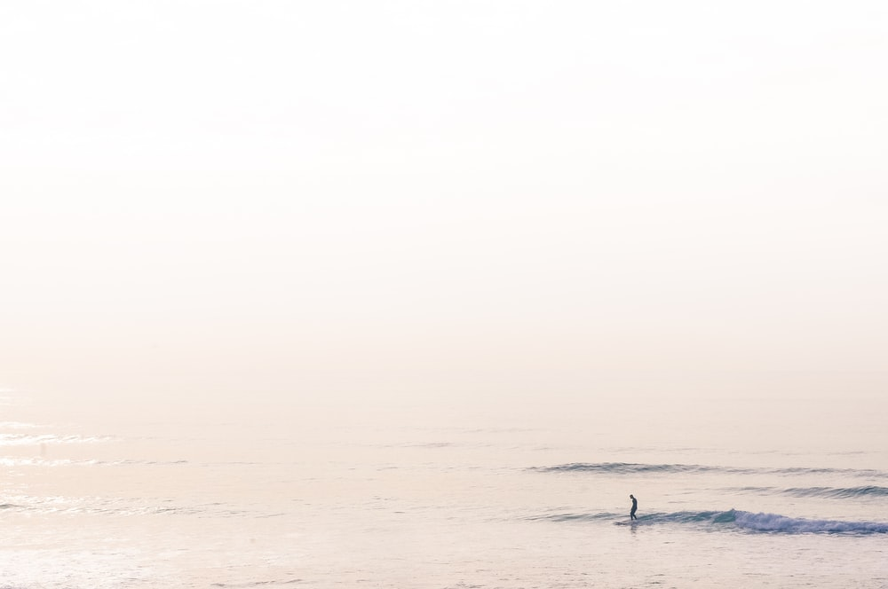 silhouette of man surfing on sea during daytime