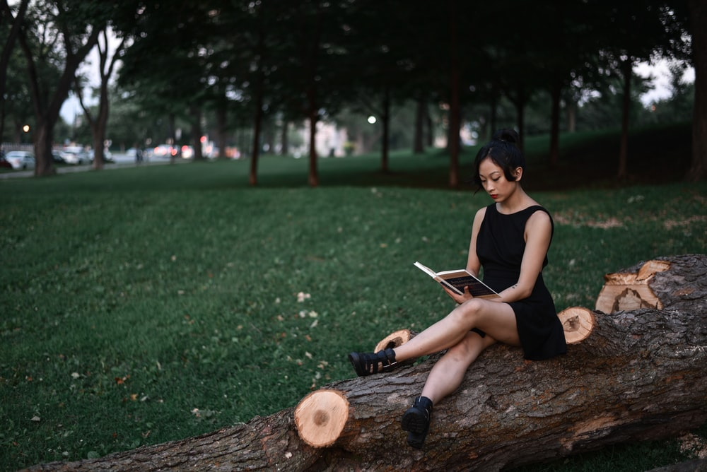 Woman sitting on a fallen log reading alone