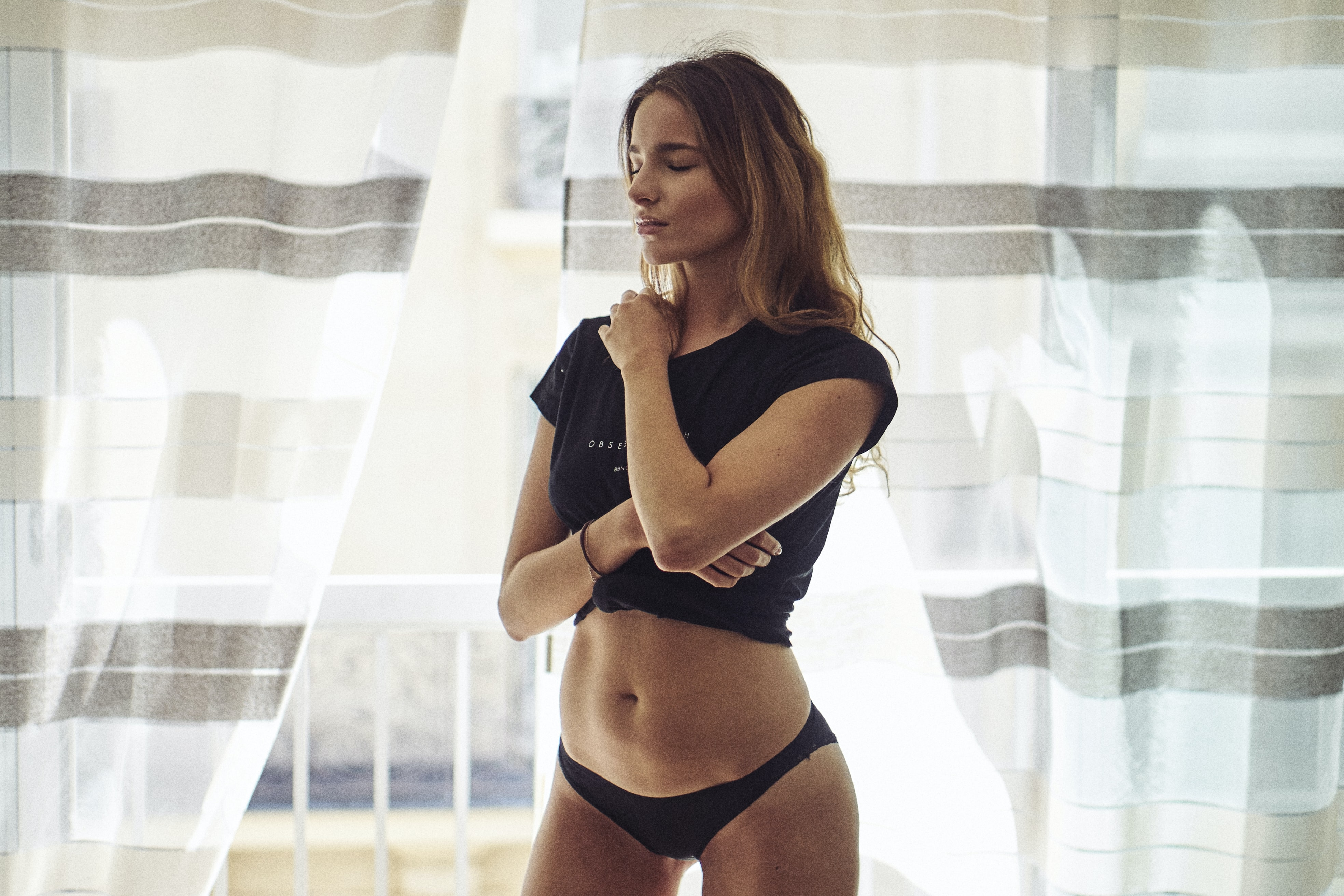 A woman wearing a black crop top and underwear with closed eyes in front of a curtain
