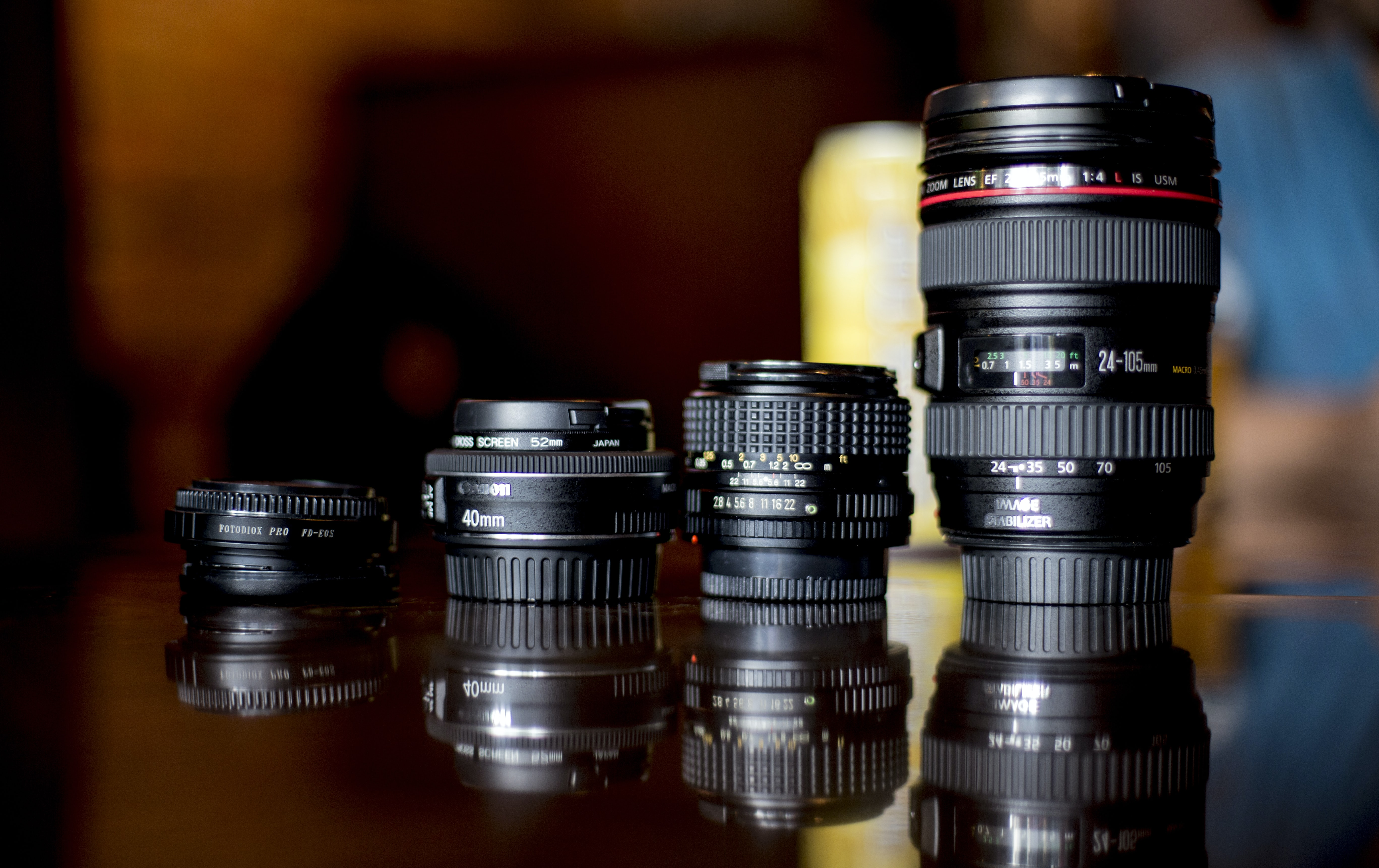 A set of various professional DSLR camera lenses lined up in a row