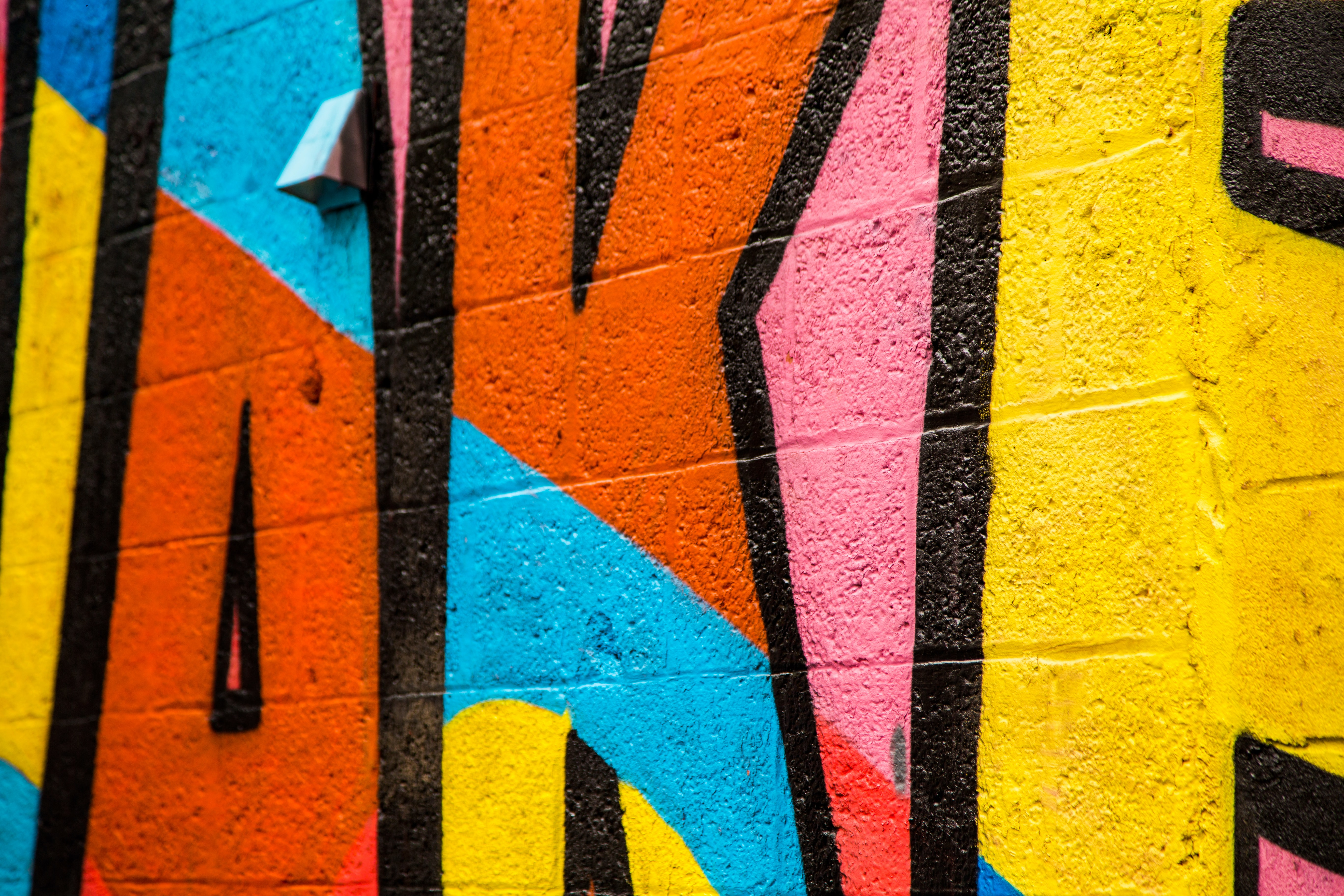 Hard to read colorful graffiti letters viewed up close.
