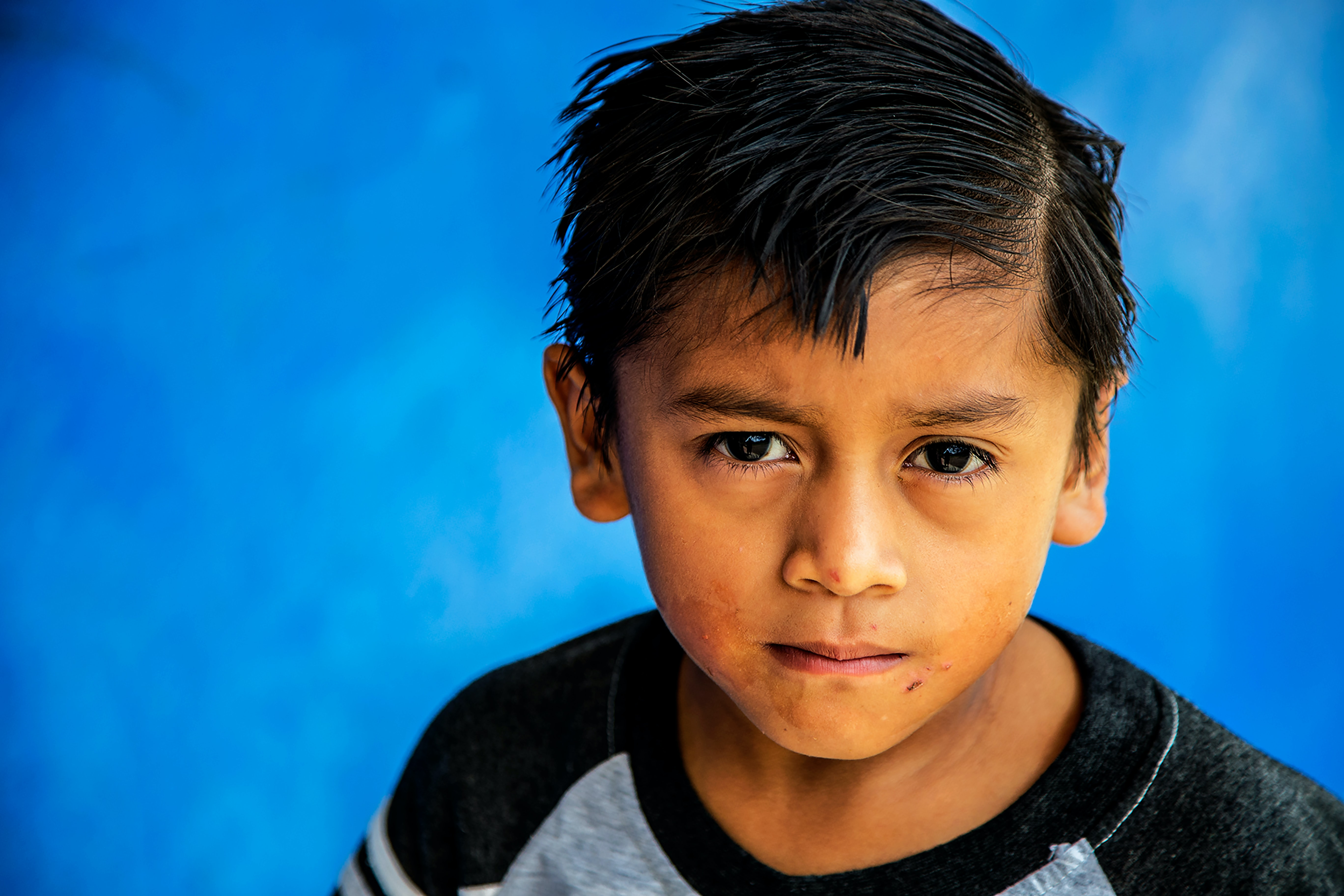 photo of boy standing against blue background