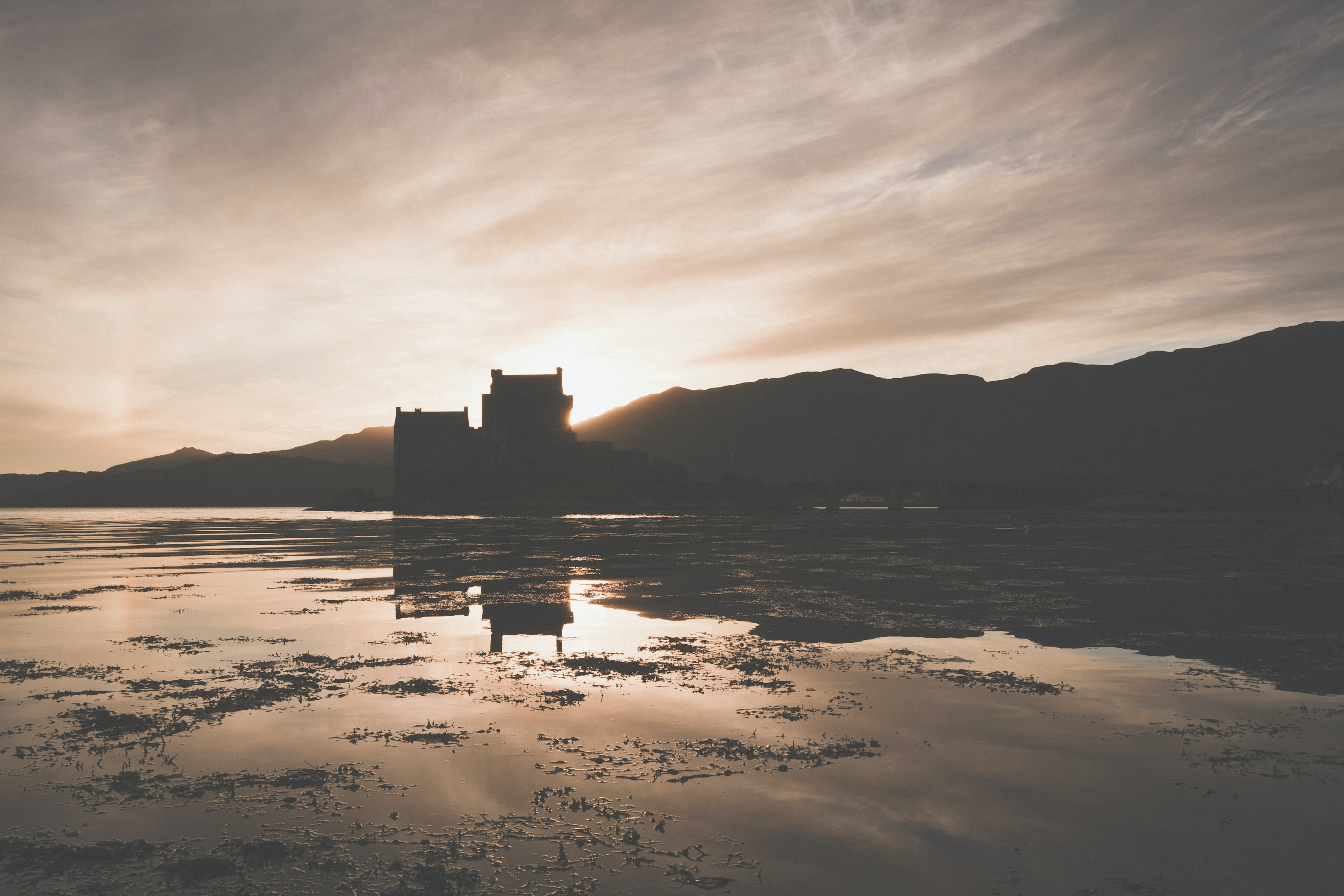 A silhouette of a castle at the shore of a lake at sunset