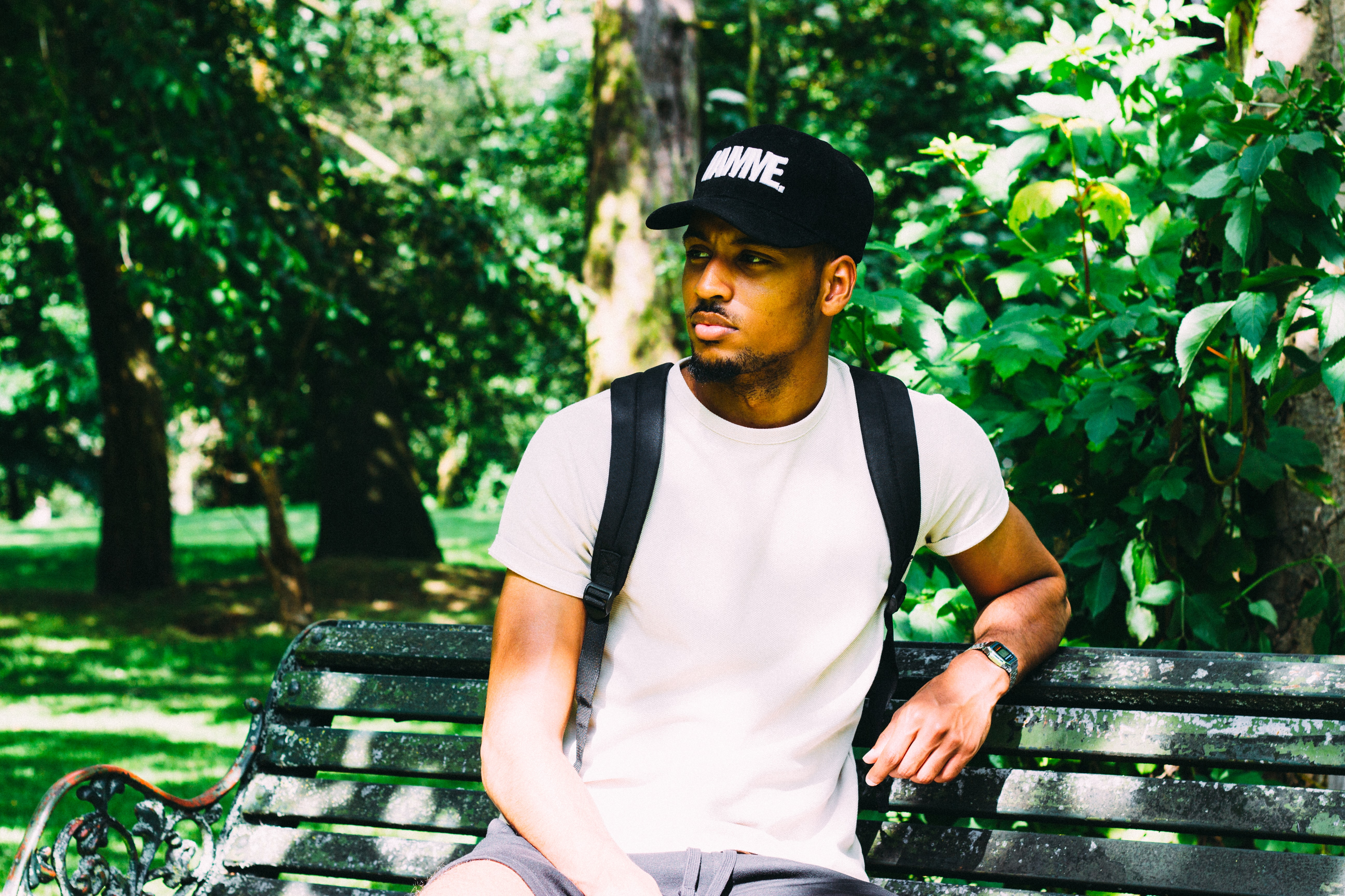 Trendy man in a hat and backpack sits alone in a park bench