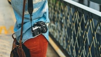 person carrying bag and camera facing fence