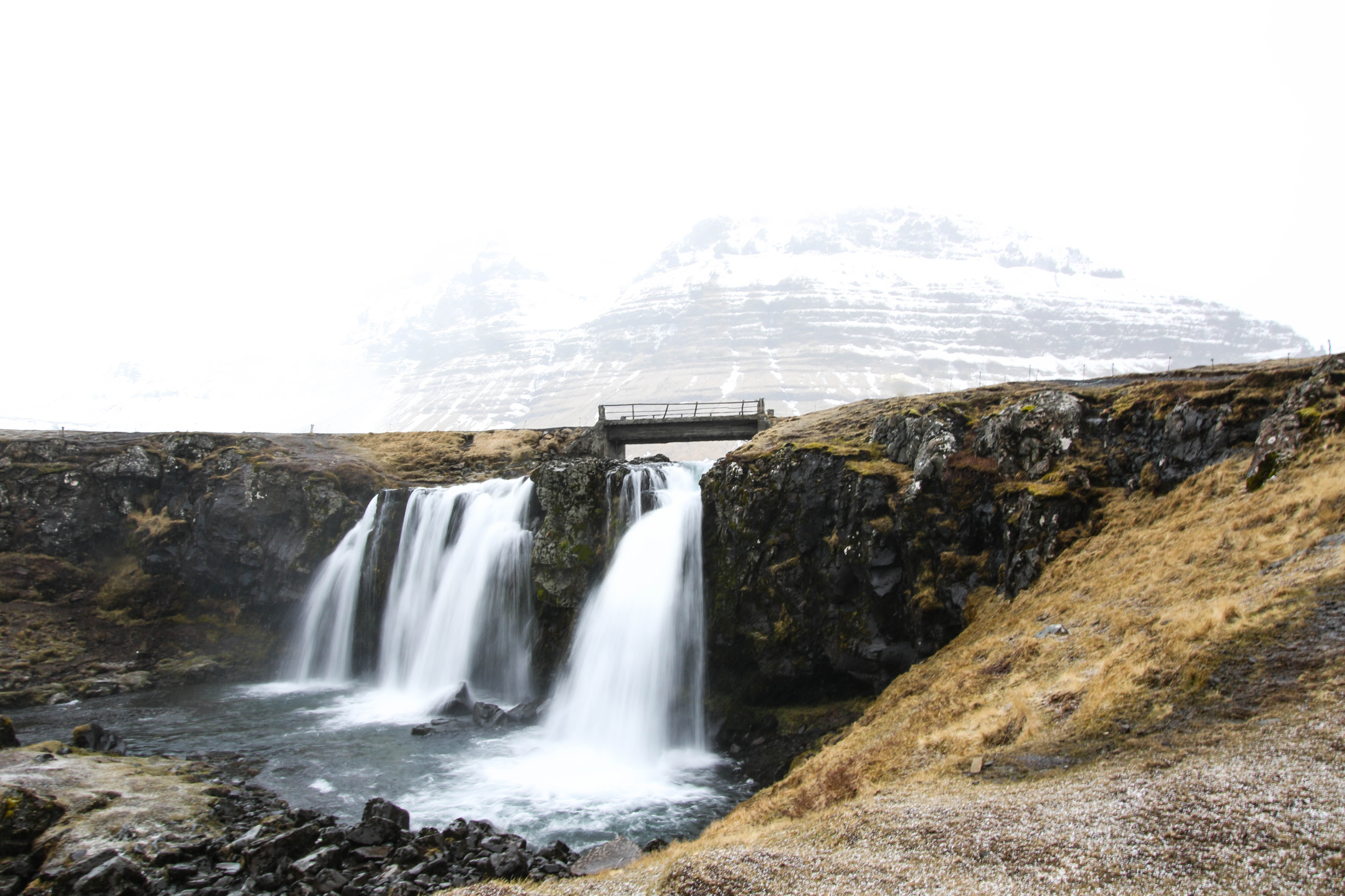 waterfalls near snow-covered mountain at daytime