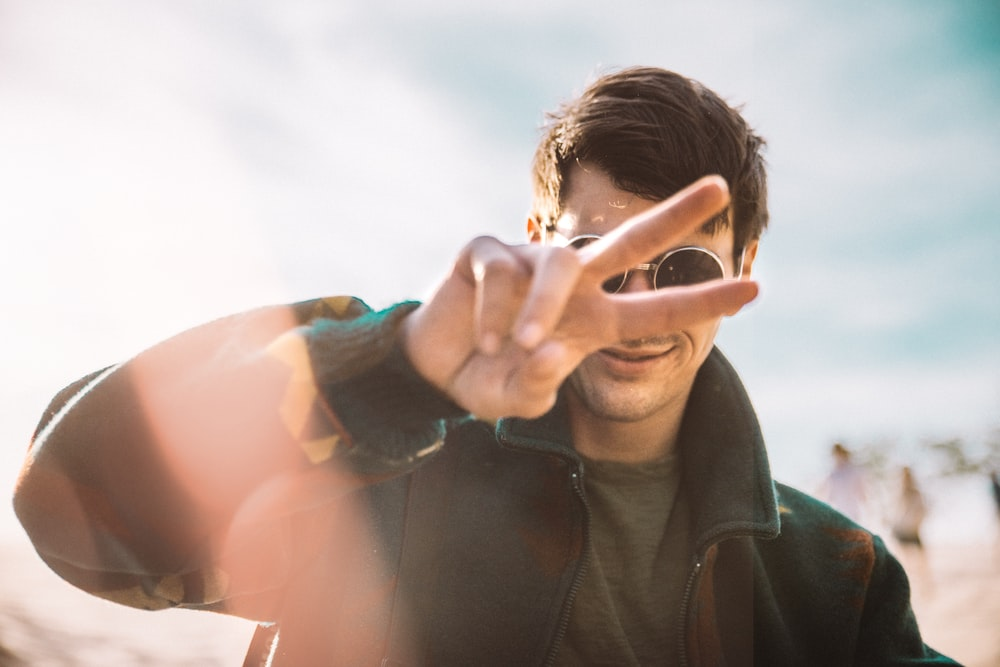 shallow focus photography of smiling man doing peace sign
