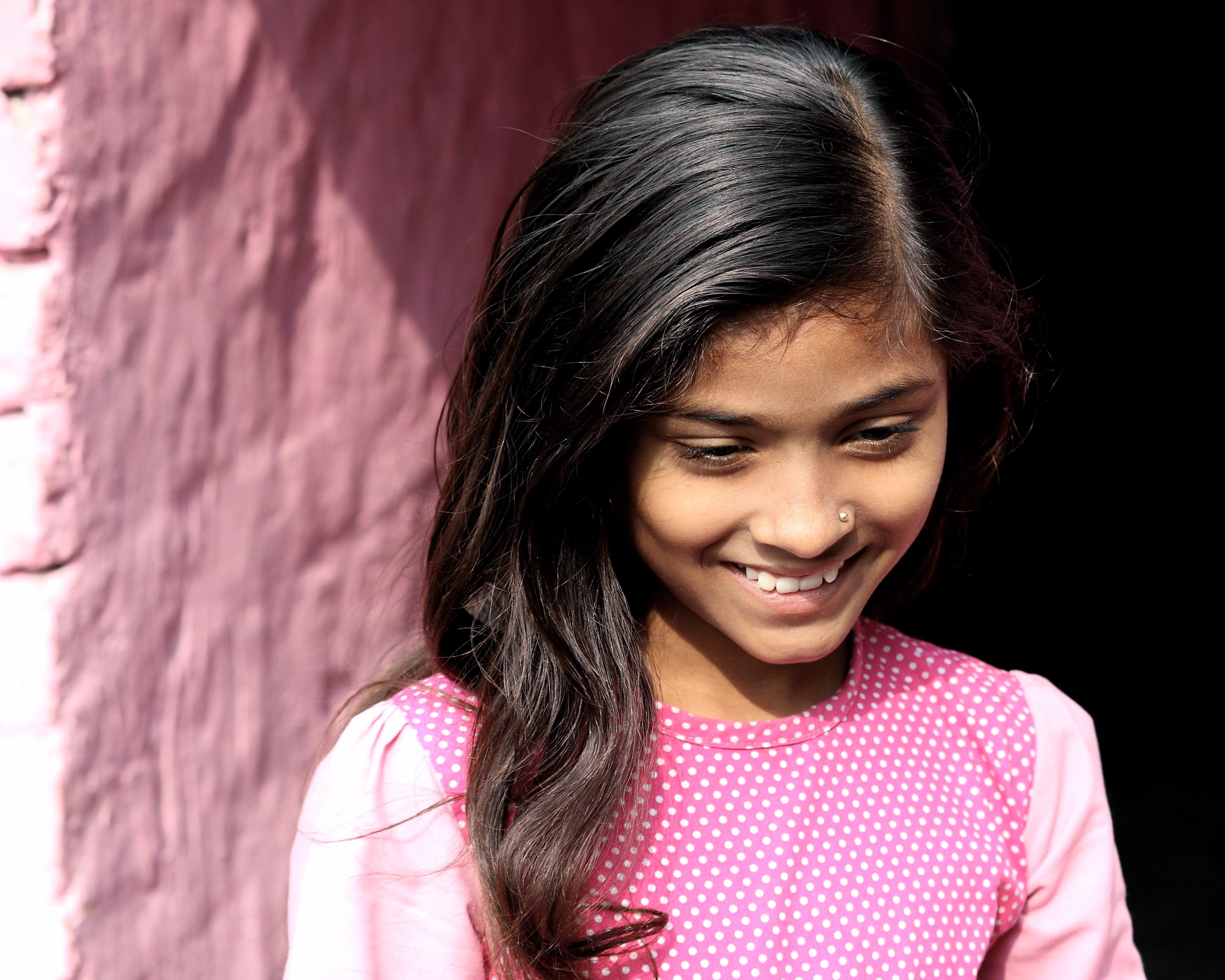 A smiling young girl in a pink shirt against a pink brick wall in Kolkata