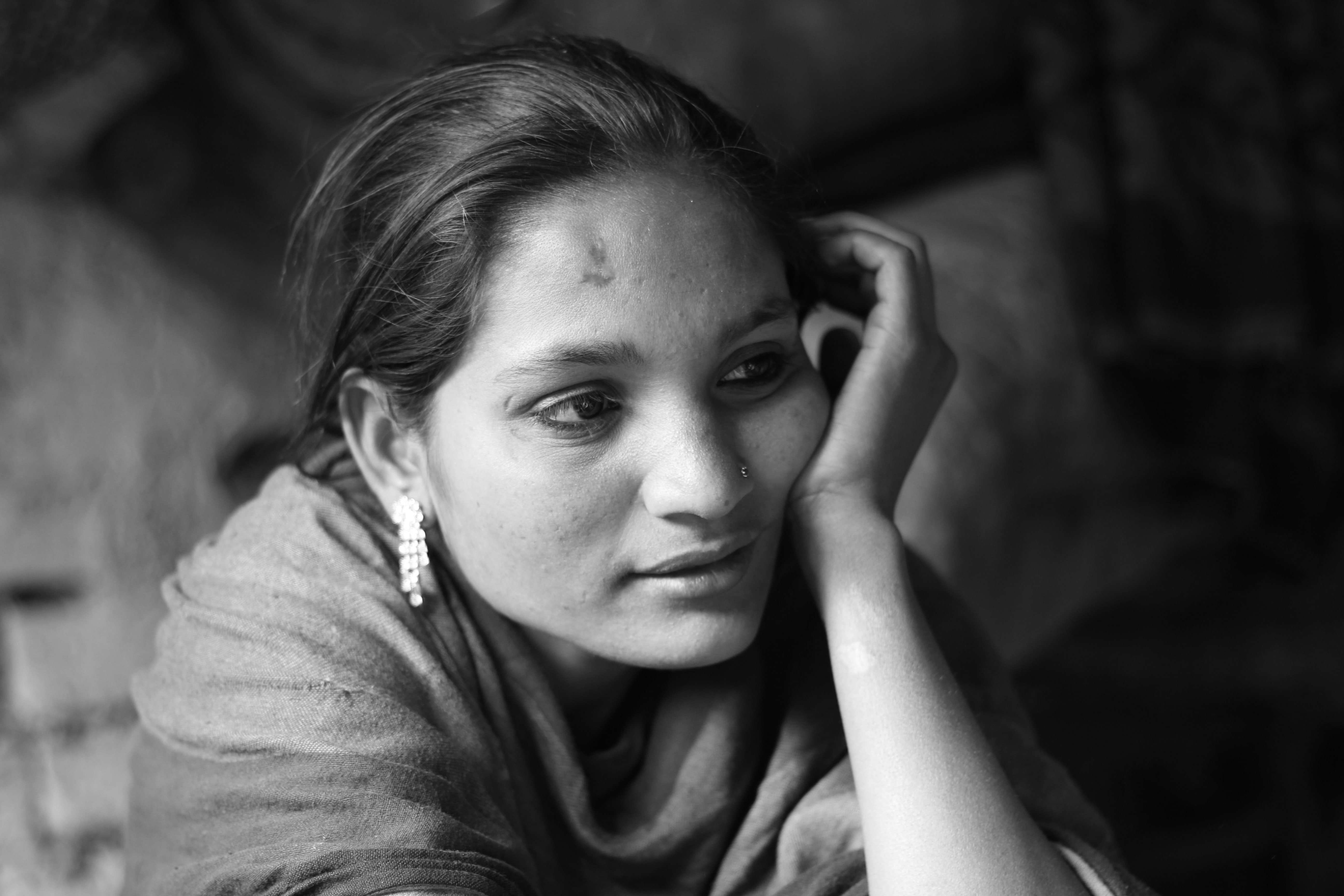 Black and white shot of woman with earring resting her face on hand in Kolkata