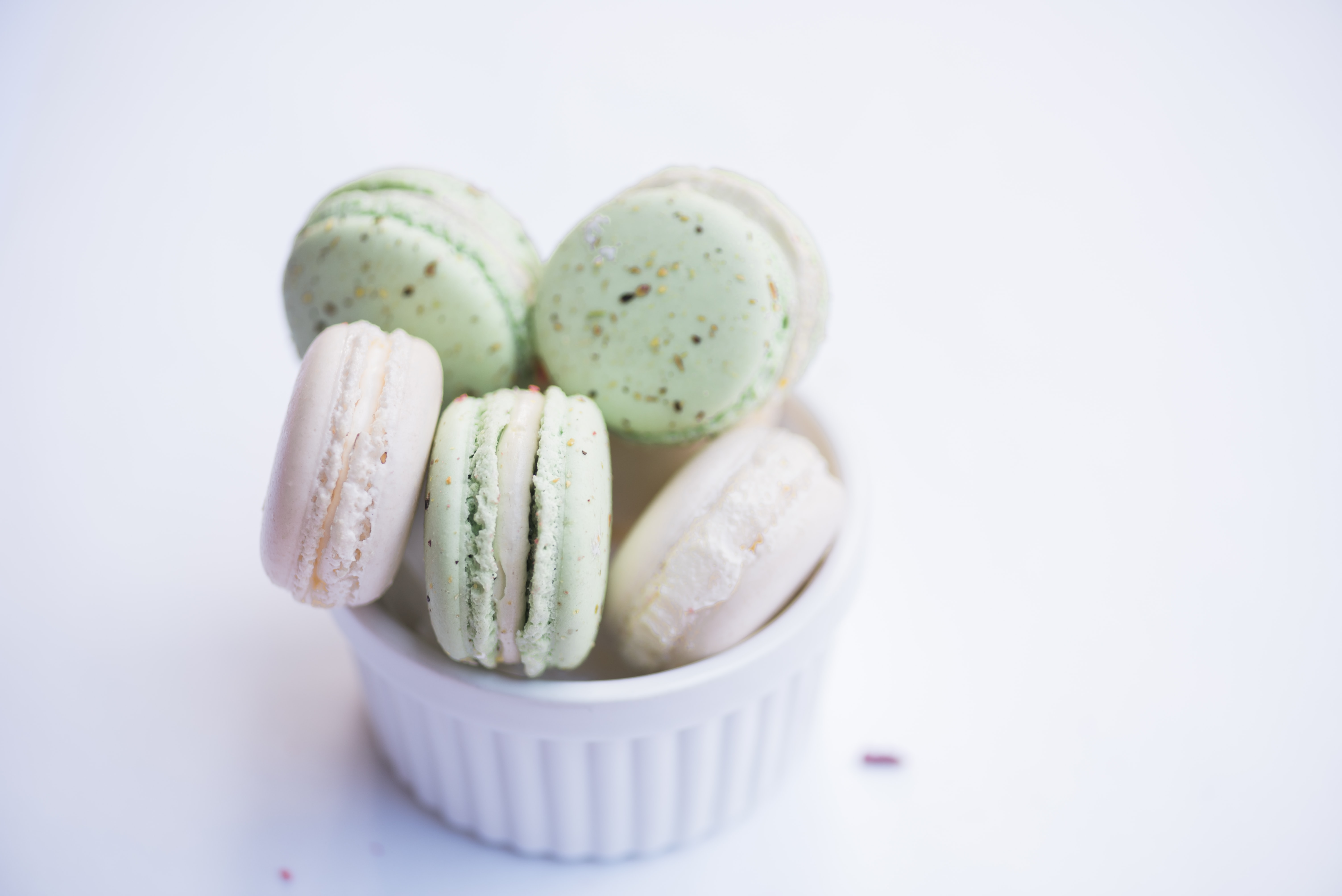 Colorful macaroons in a small white bowl on a white surface