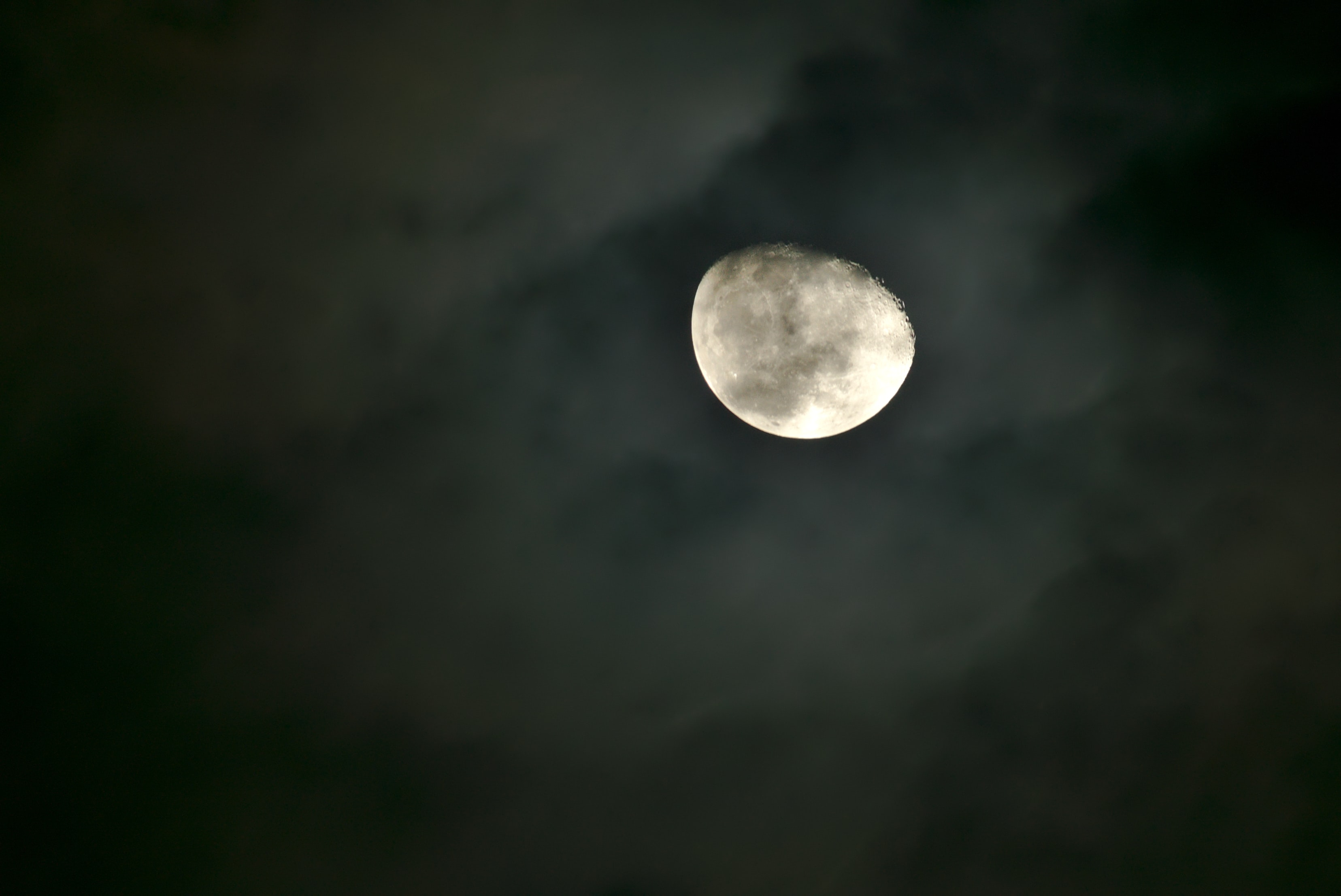 A bright moon in the night sky surrounded by wispy clouds