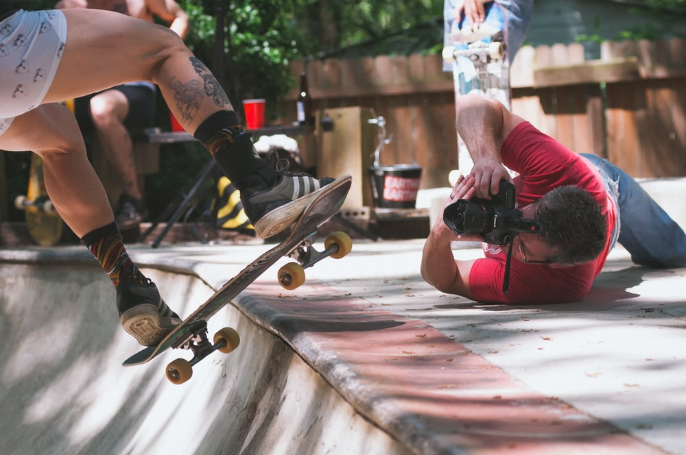 man lying on floor while taking picture of person doing skate trick on ramp