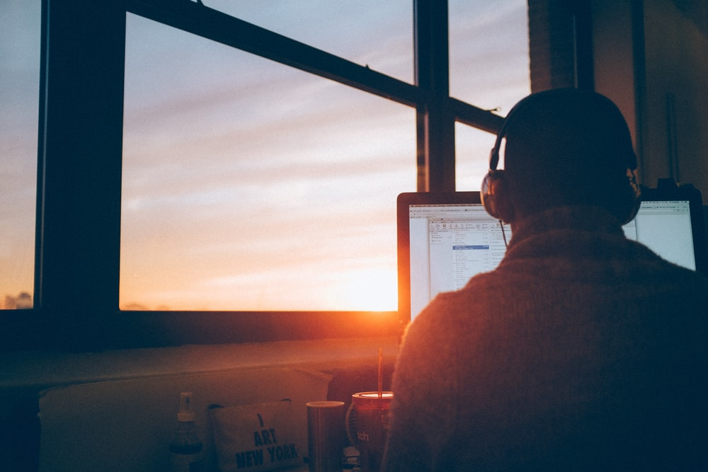 Man wearing headphones at desk with window view of sunset in background