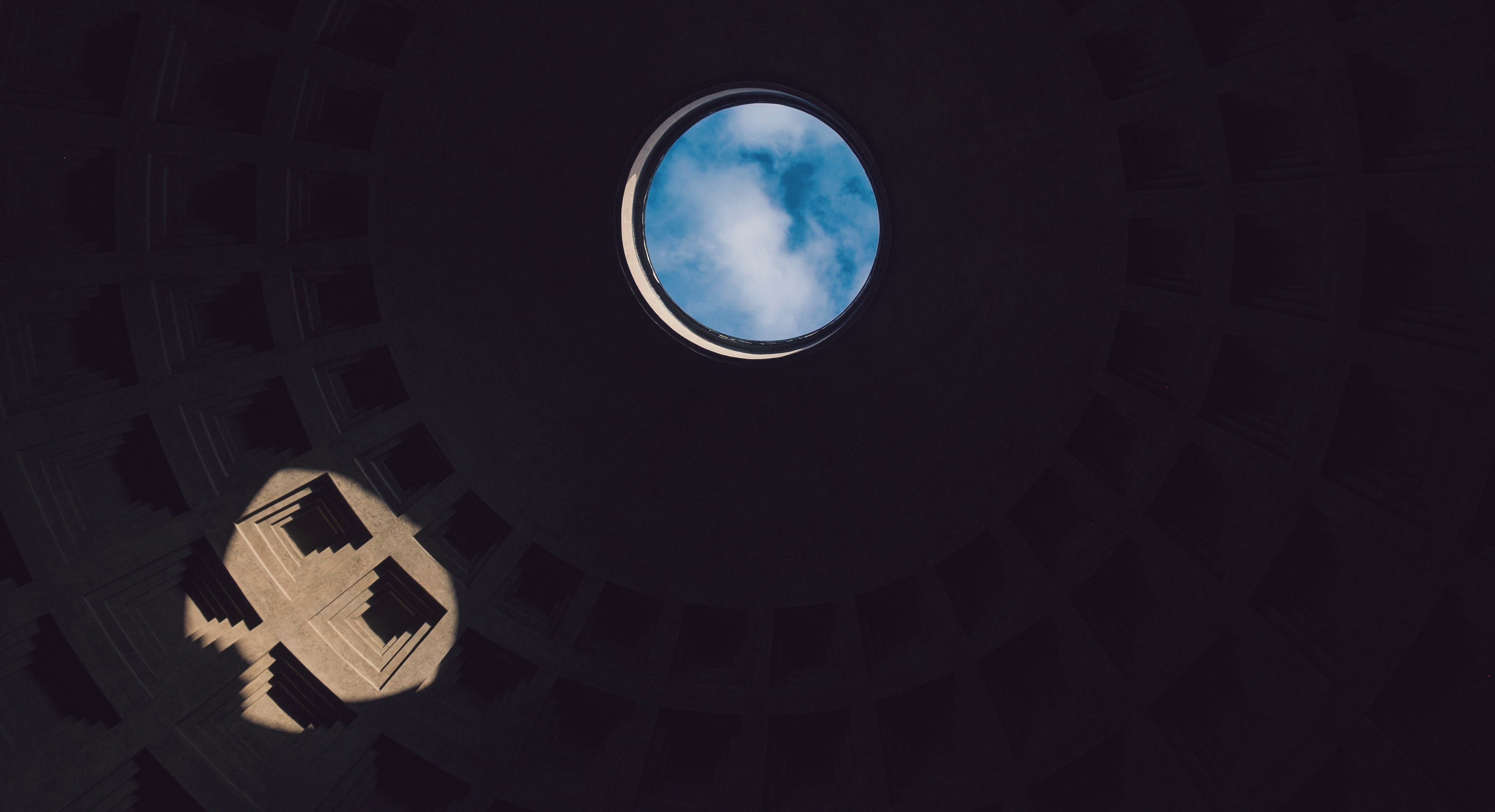 Blue sky seen through the oculus in the concrete dome of the Roman Pantheon