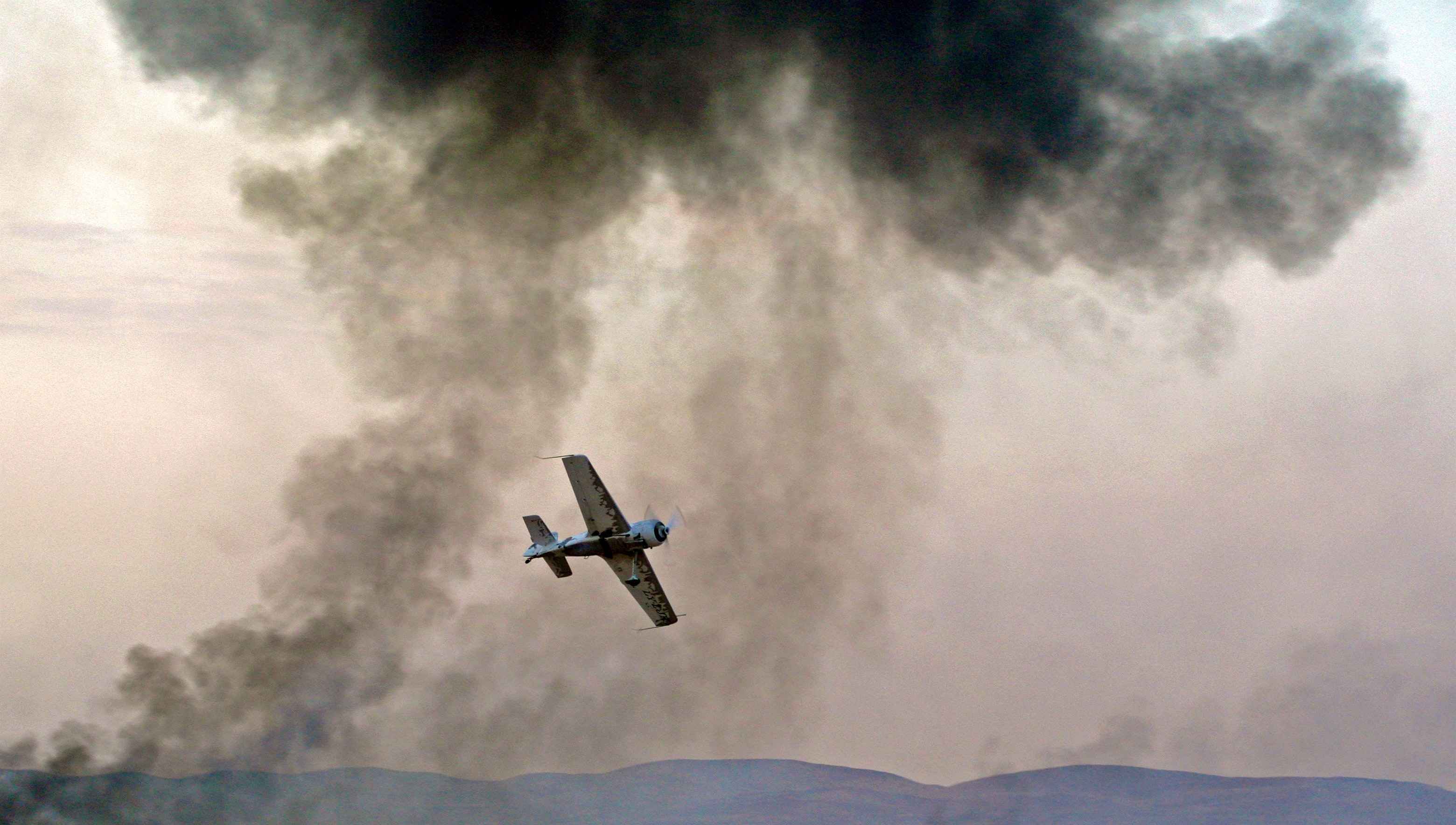 panning photography of flying blue and white biplane