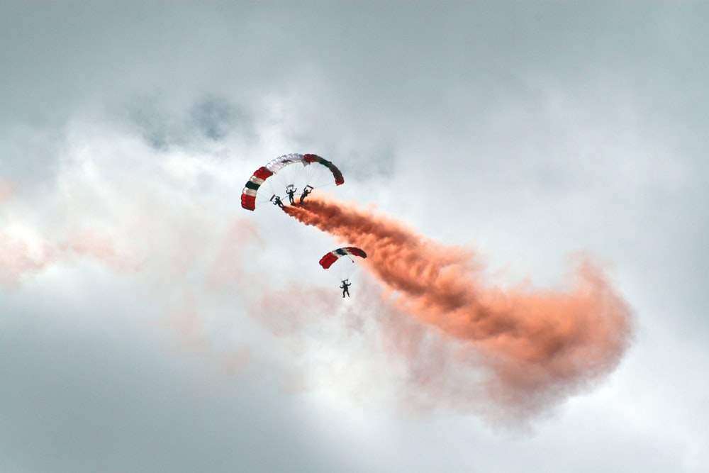 worms eye view photography of people paragliding under cloudy sky