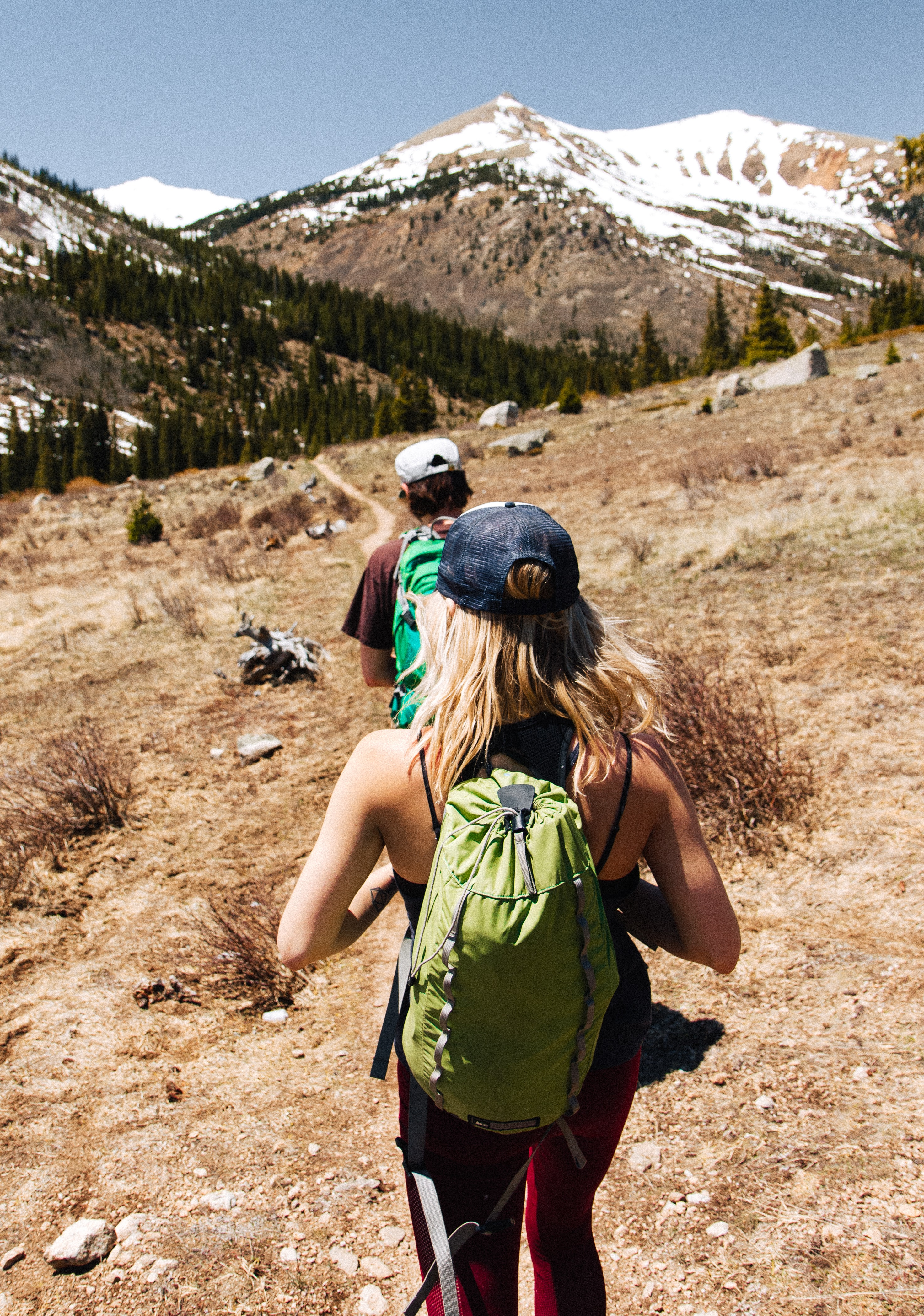 man and woman hiking on brown and white mountain