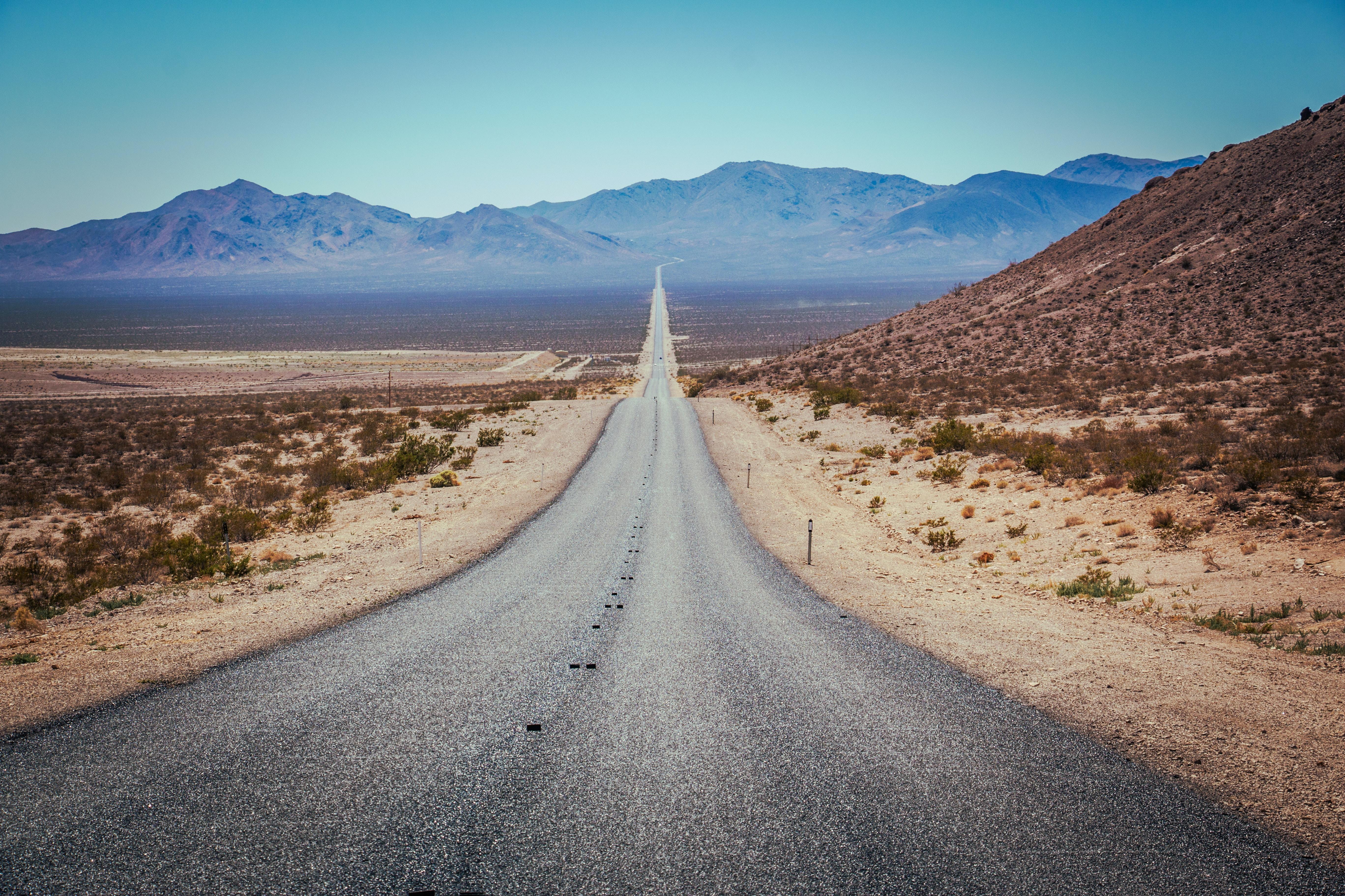 grey asphalt road heading mountain