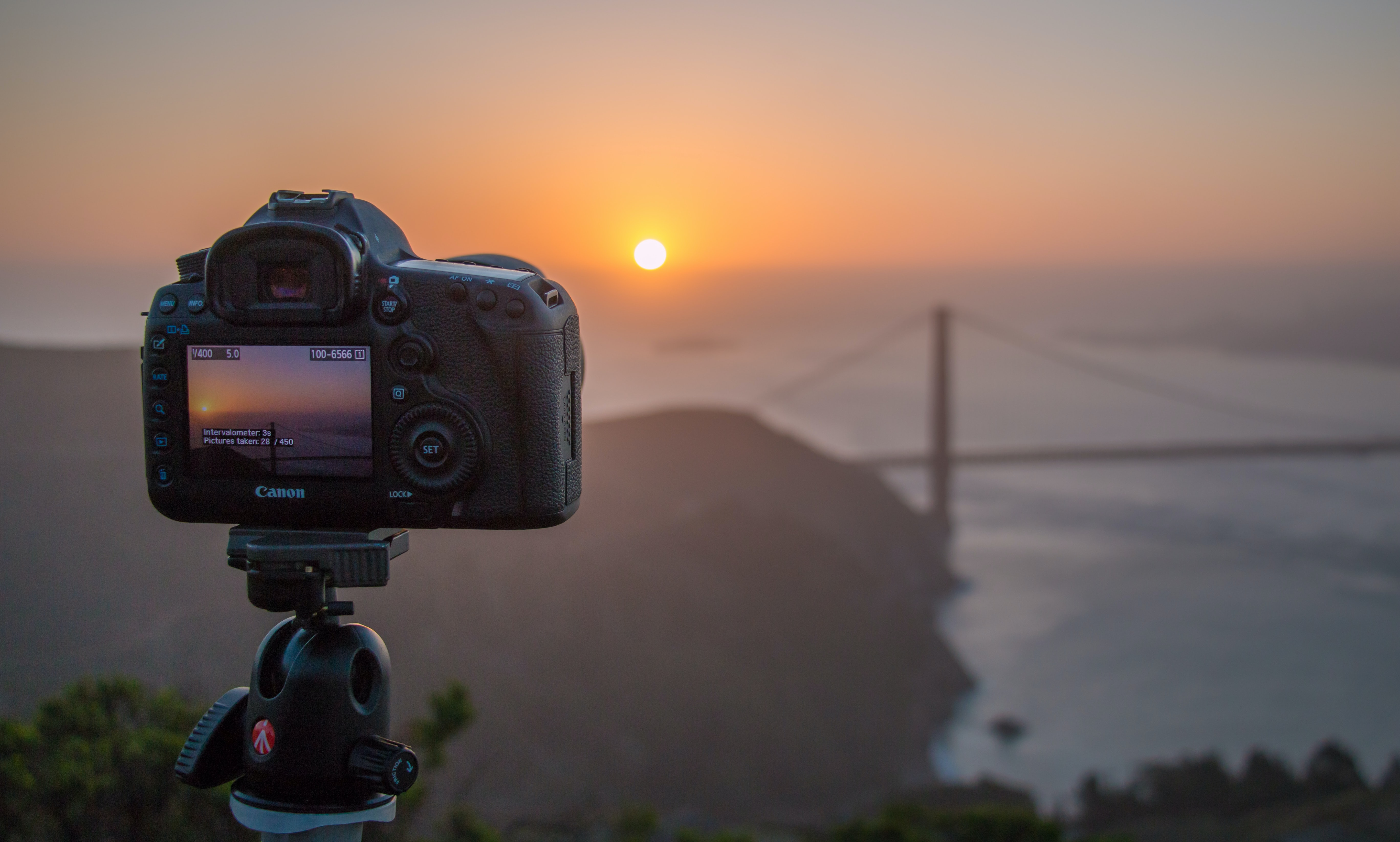 A close-up of a Canon camera photographing the Golden Gate Bridge during sunrise.