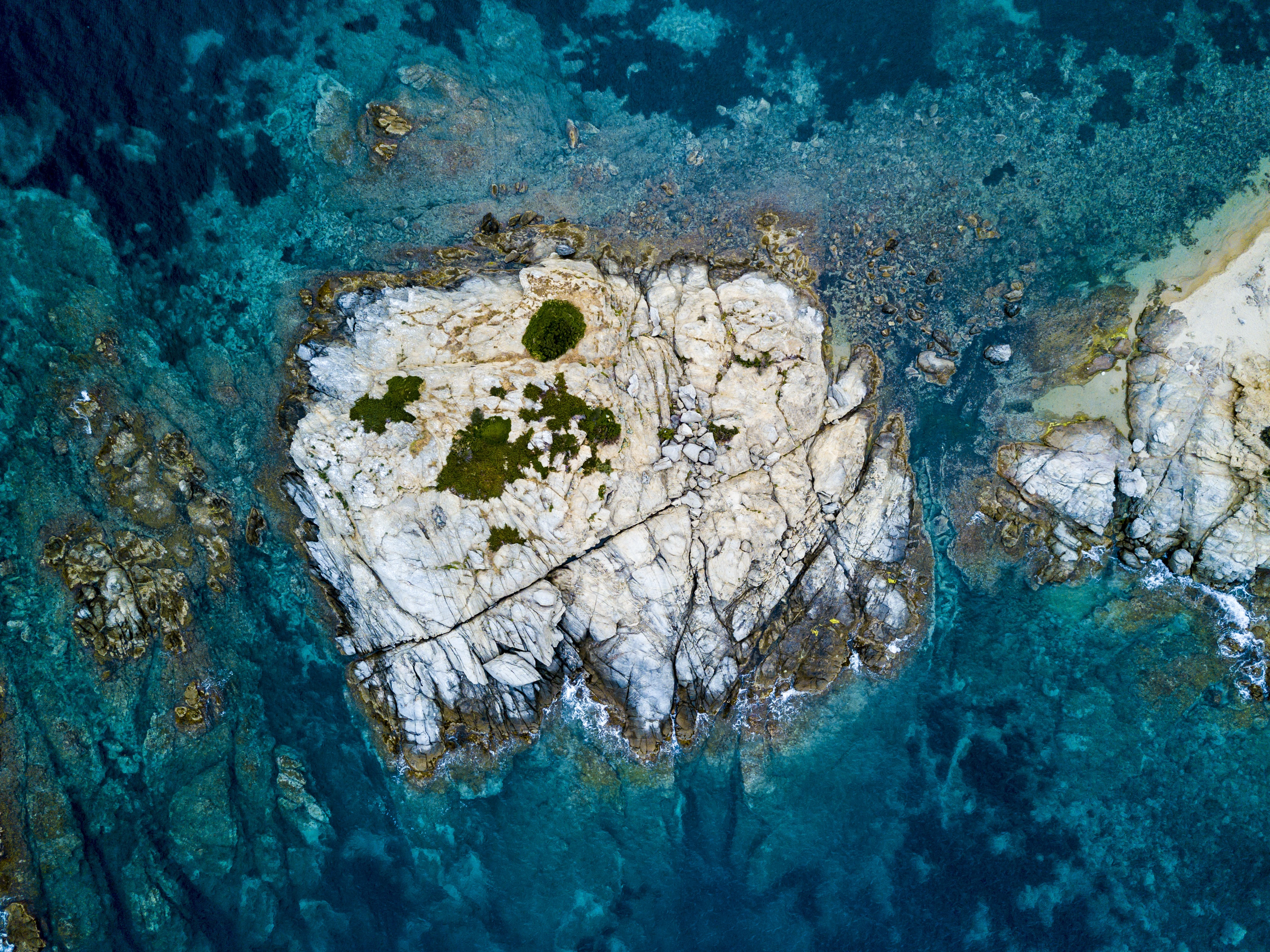 A drone shot of a rocky island in the sea