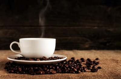 white ceramic mug and saucer with coffee beans on brown textile coffee zoom background