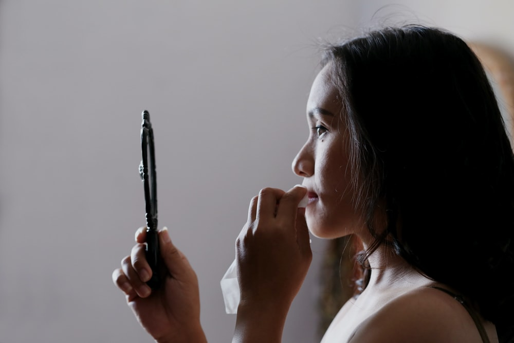 woman looking to mirror and wiping her lips