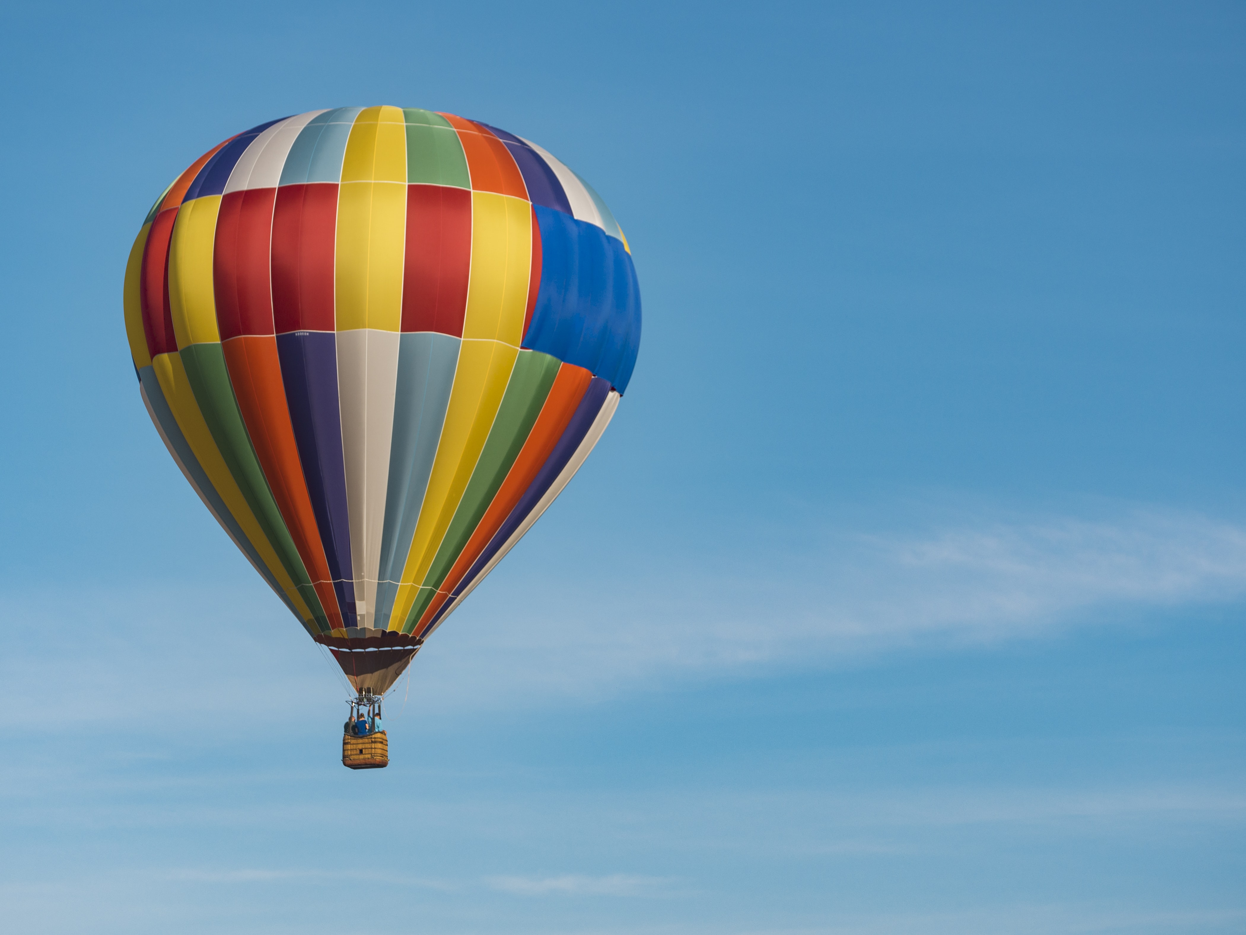 Three people in the basket of a colorful hot air balloon floating against a blue sky