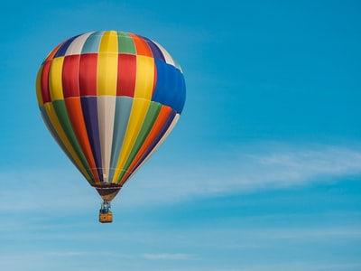 panning photography of flying blue, yellow, and red hot air balloon hot air balloon zoom background