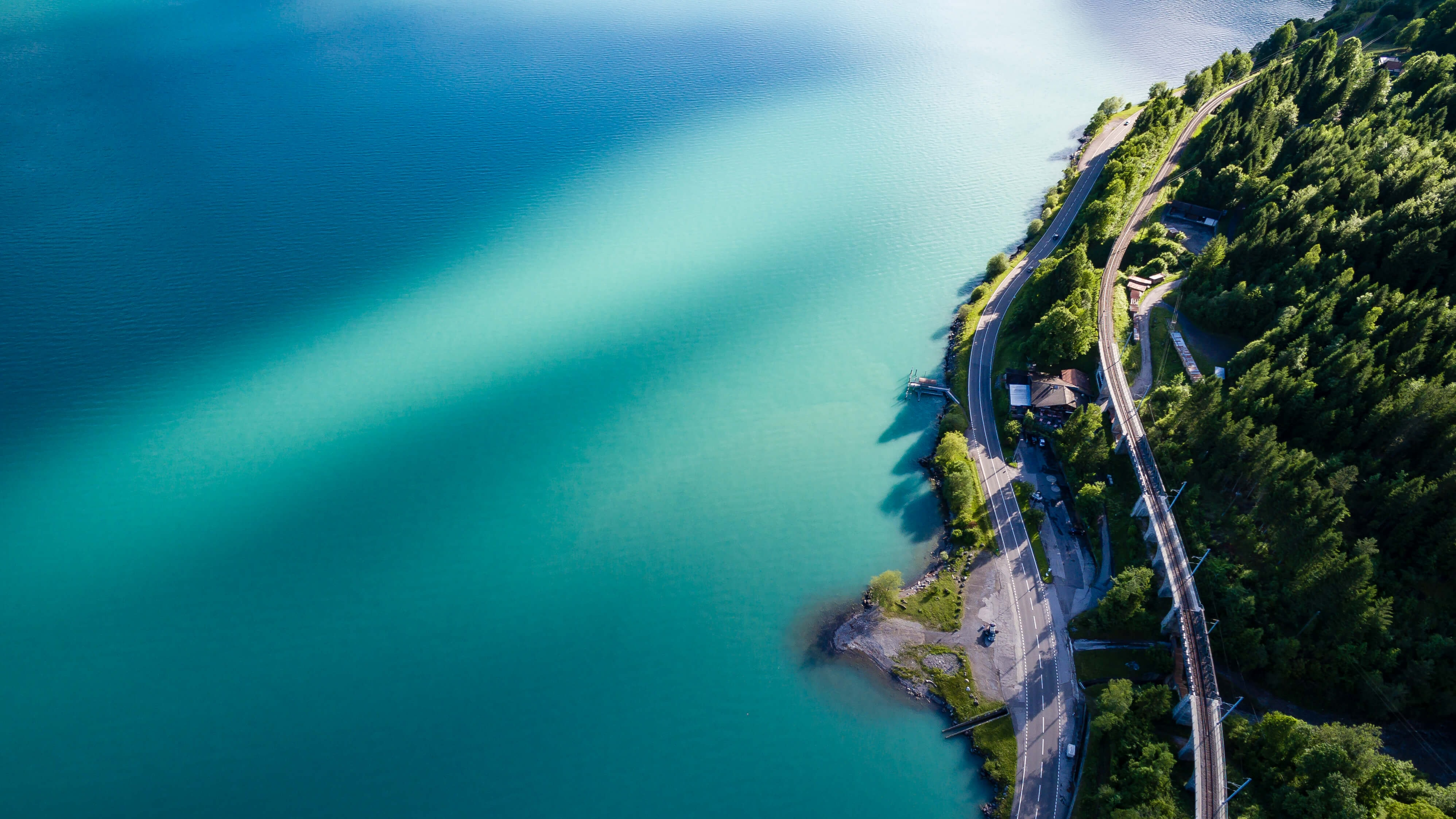 Two roads running along the shore of the blue Lake Brienz