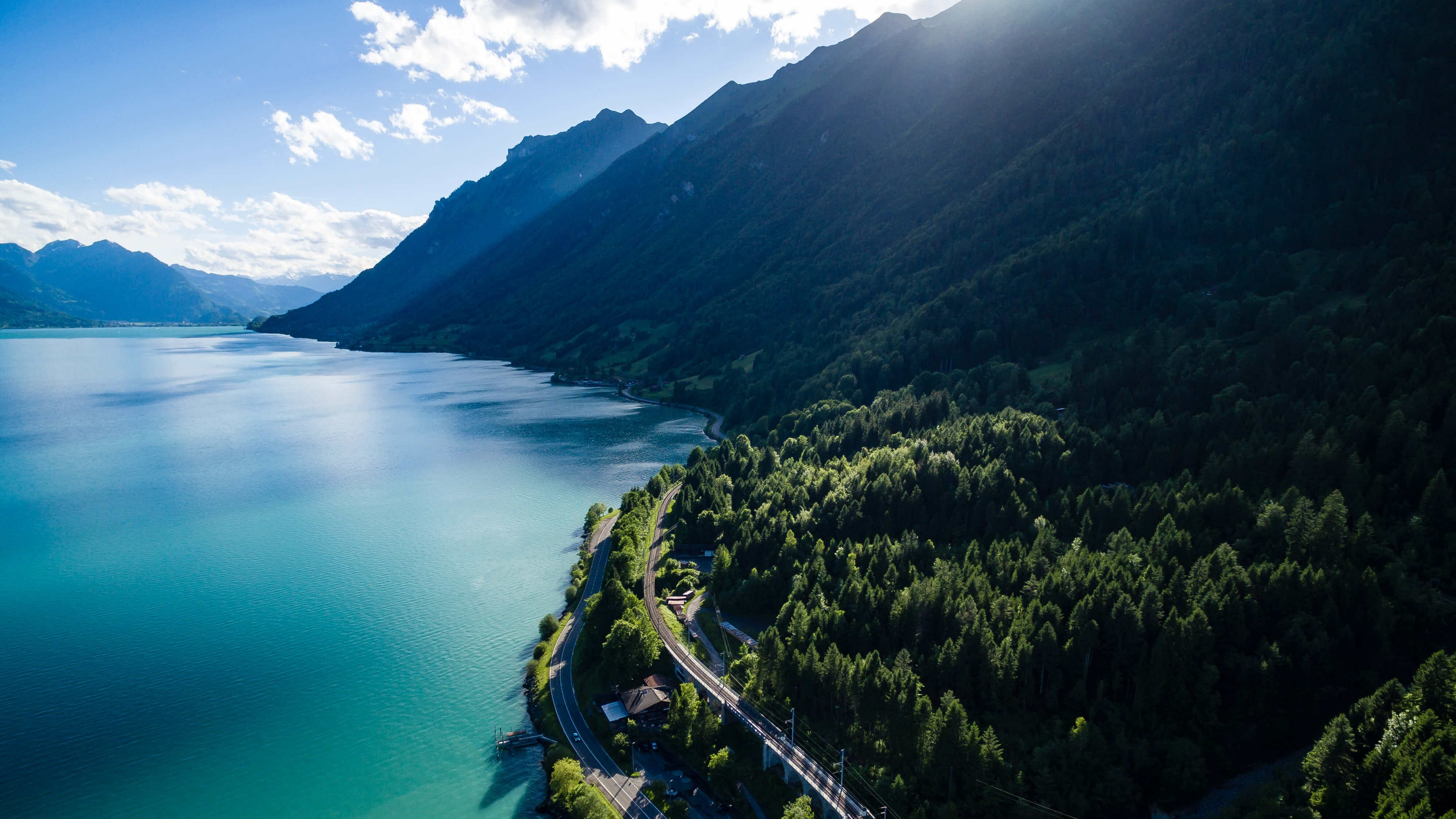 A drone shot of two parallel roads running along the wooded shore of an azure lake