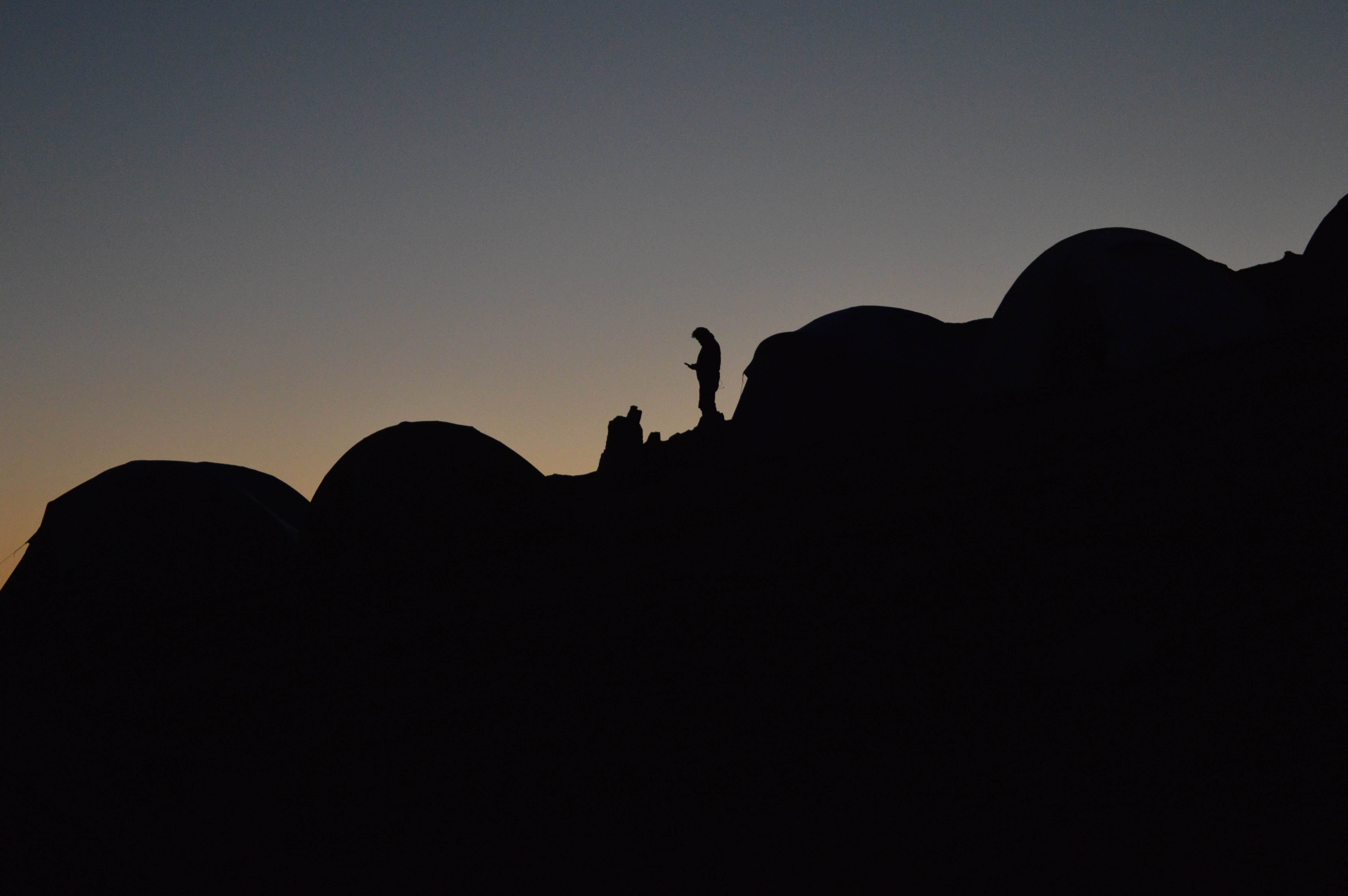 A silhouette of a person in a camping site on a slope at night