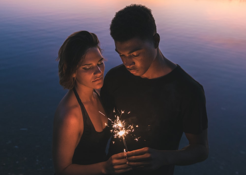 man and woman holding sparkler near body of water